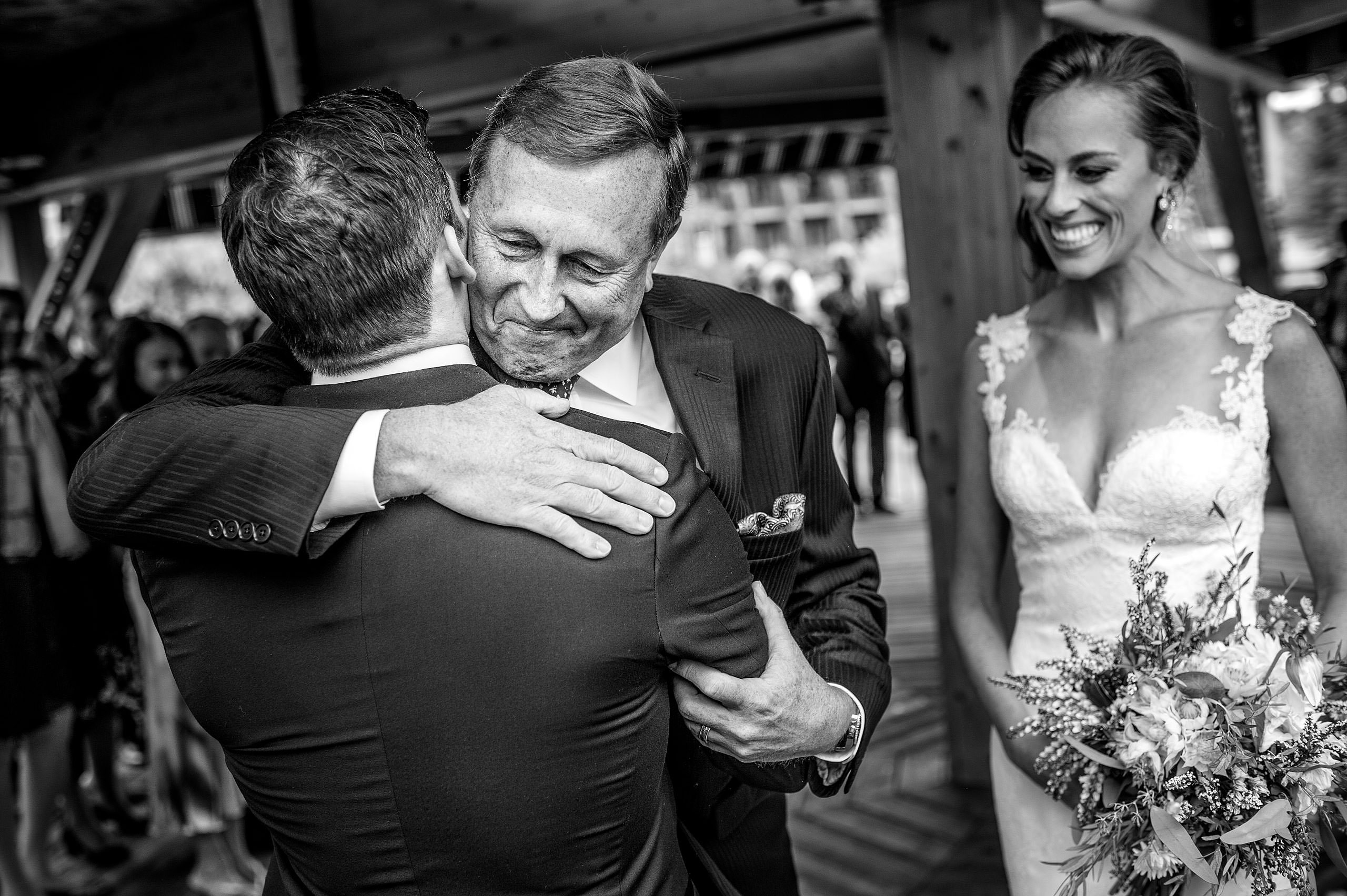 a bride's dad giving the groom a big hug at Priddis Azuridge Wedding by sean leblanc
