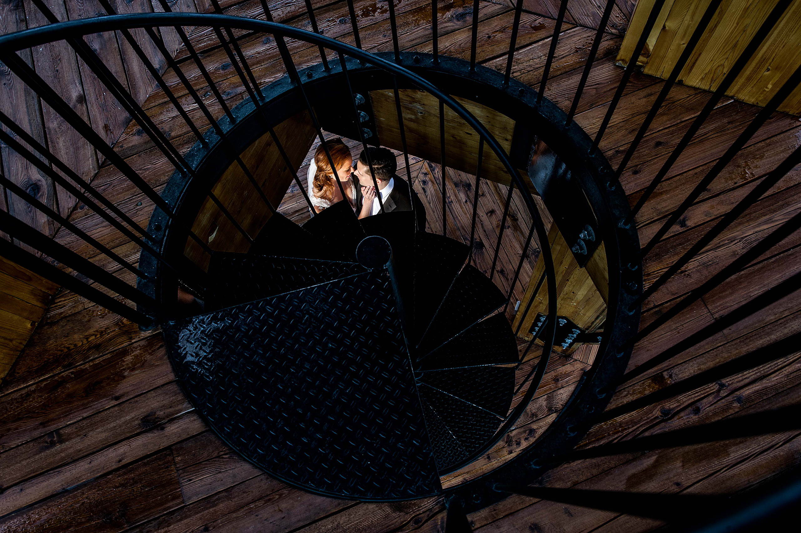 bride and groom embracing under some stairs by top calgary wedding photographer sean leblanc