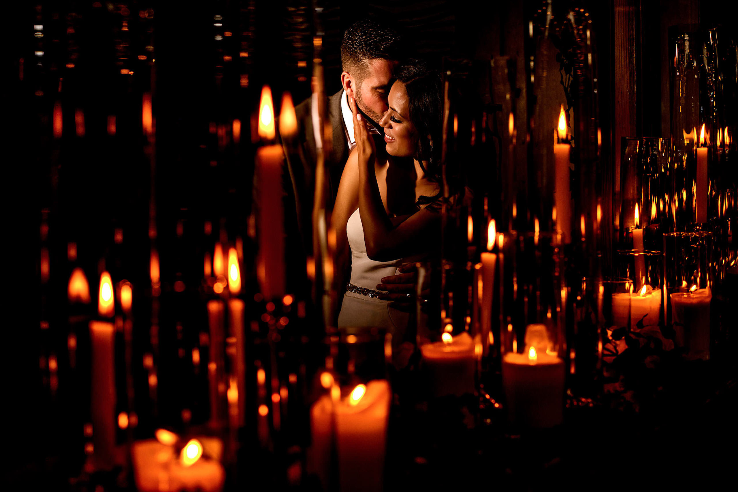 a bride and groom embracing in front of candles by calgary sean leblanc wedding photographers