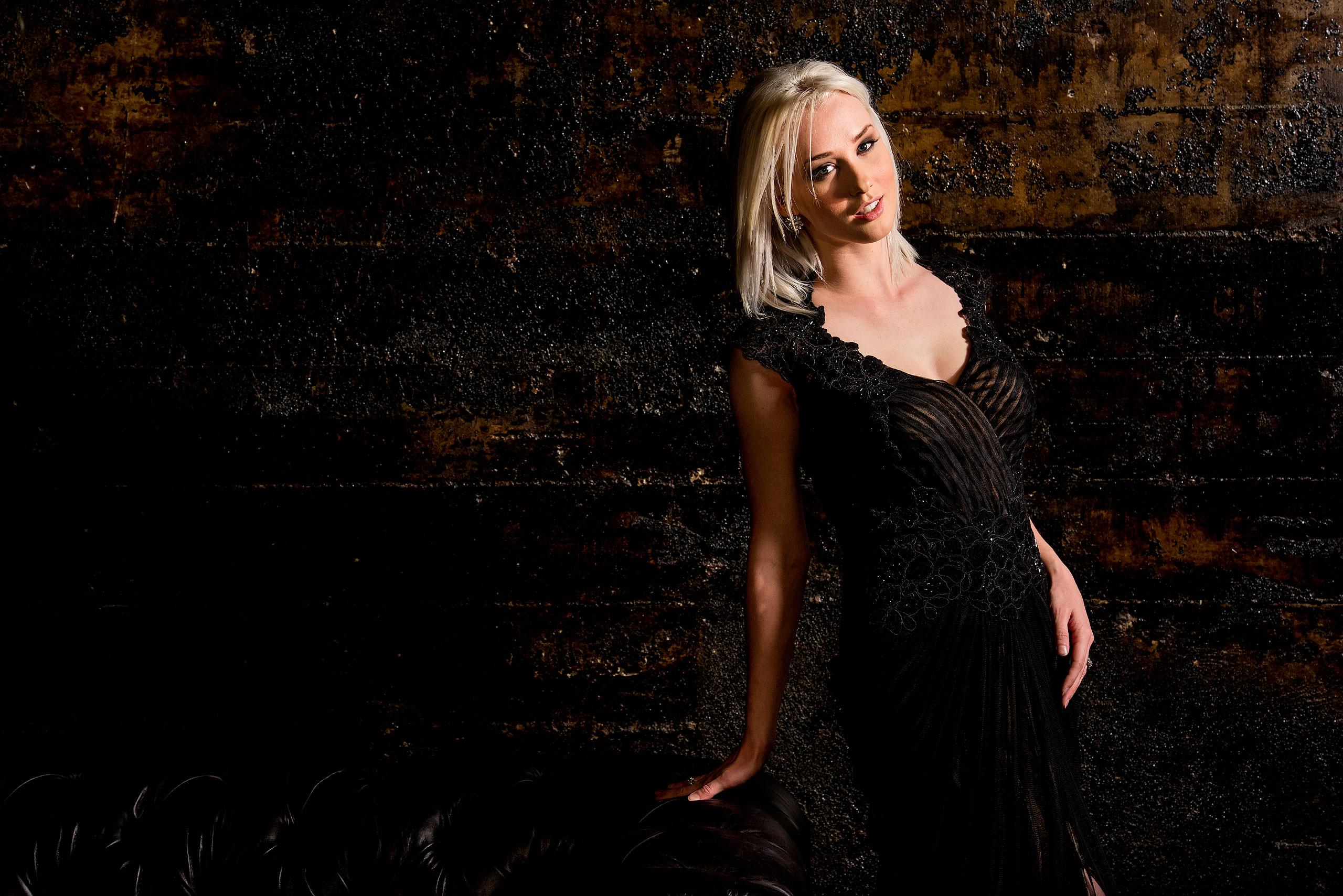 a model wearing a black dress leaning against a couch by calgary confetti fashion photographer sean leblanc