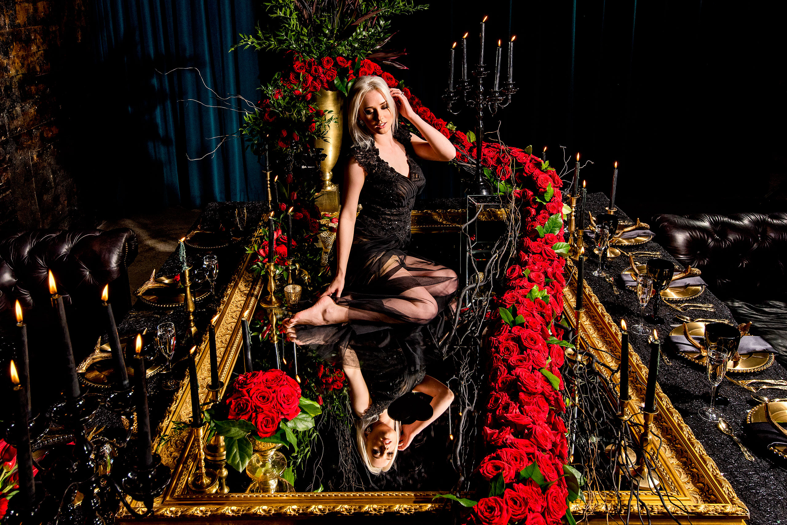 a model posing on a mirror surrounded by roses by calgary confetti fashion photographer sean leblanc