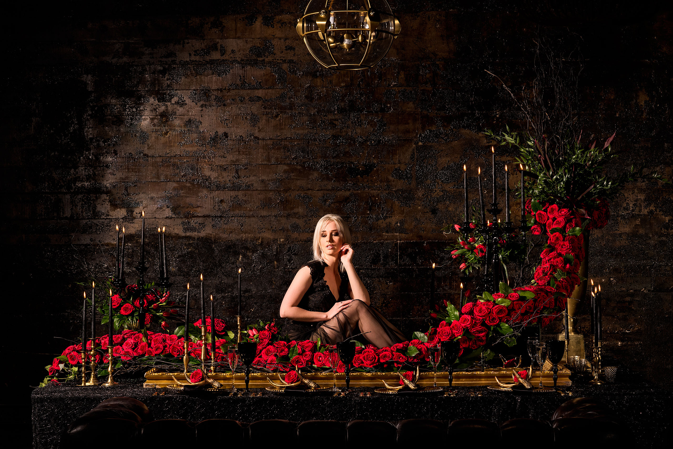 young female model posed on a table surrounded by roses