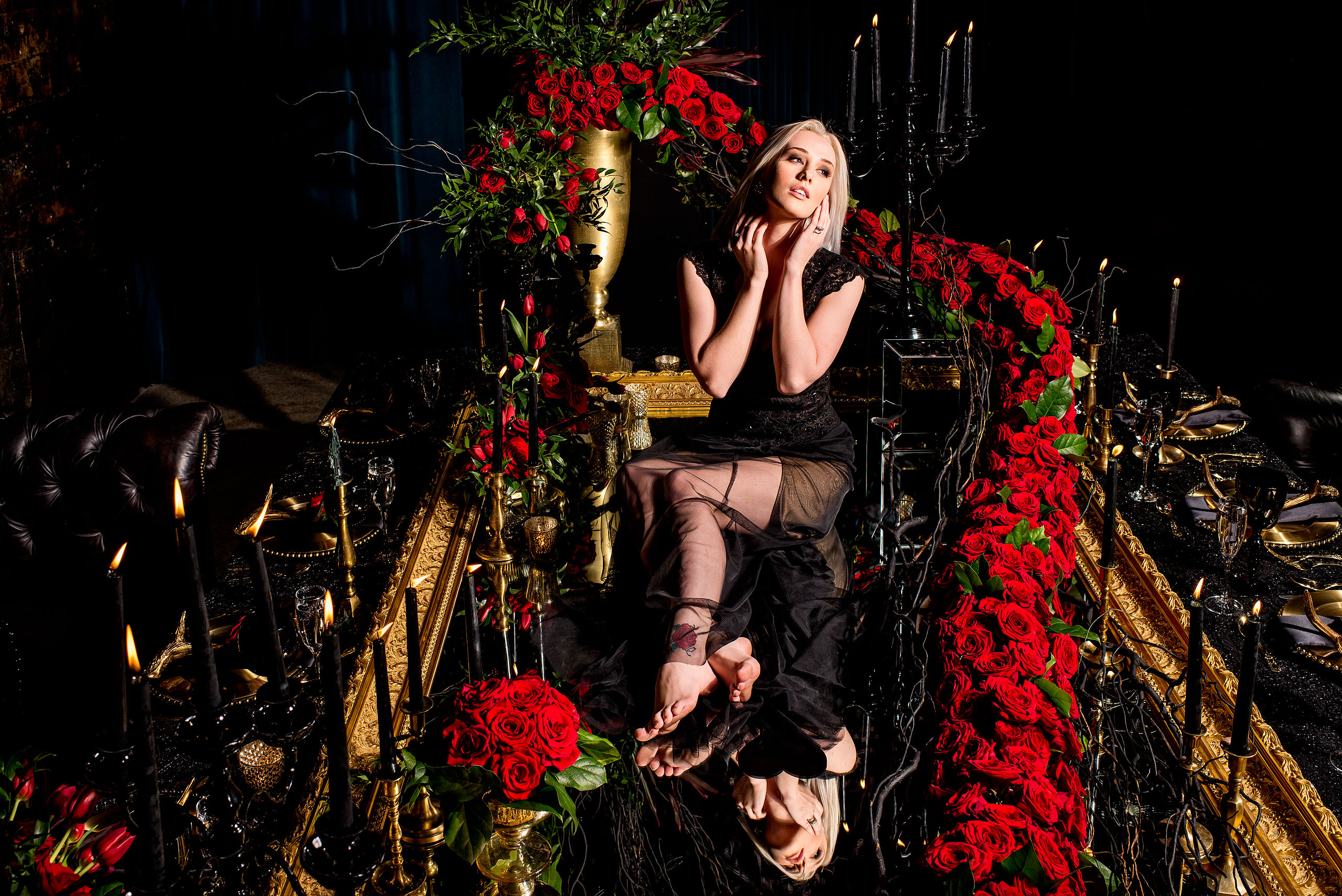 young female model sitting on a table surrounded by roses by calgary confetti fashion photographer sean leblanc