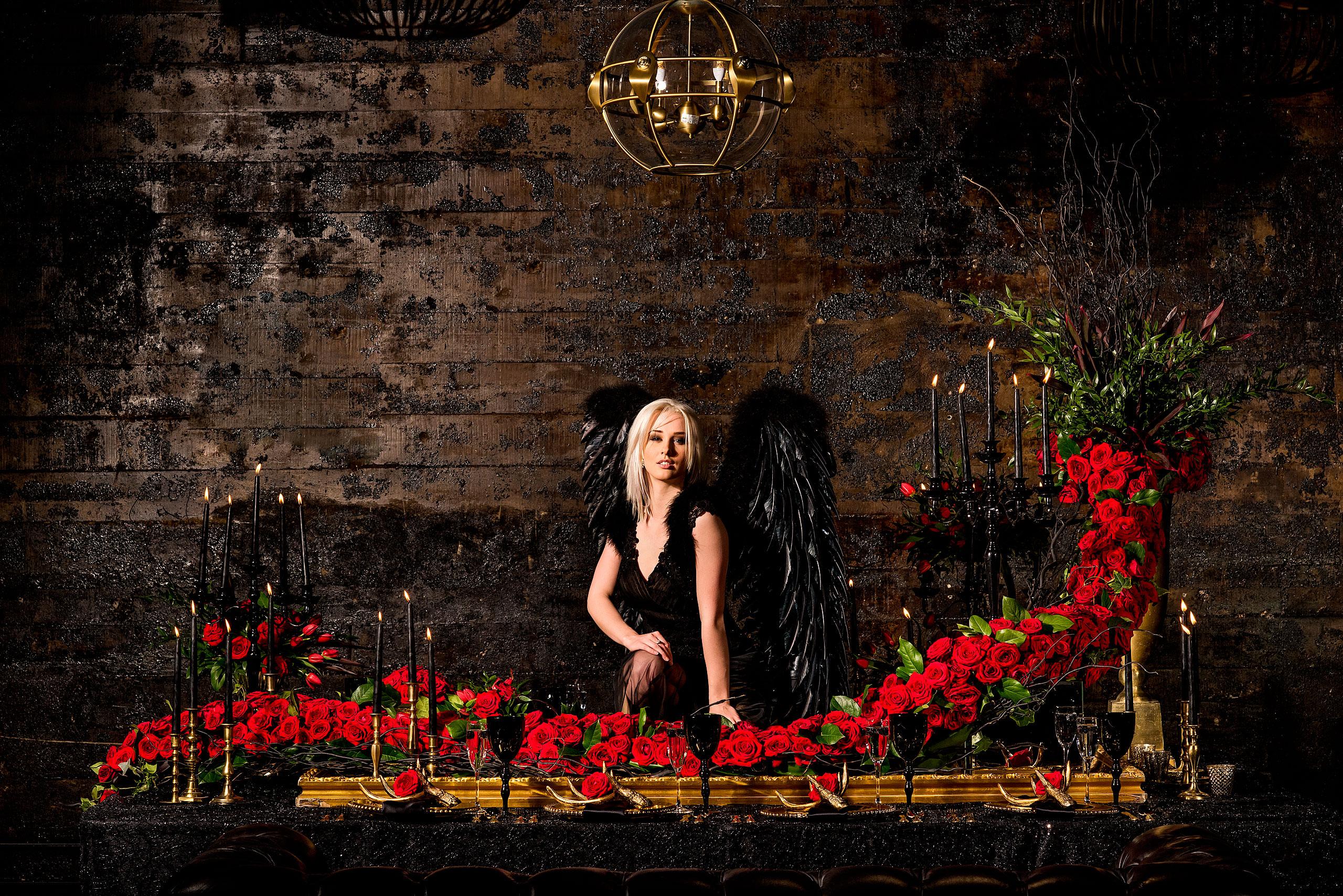 a model wearing a black dress sitting on a mirror behind roses by calgary confetti fashion photographer sean leblanc
