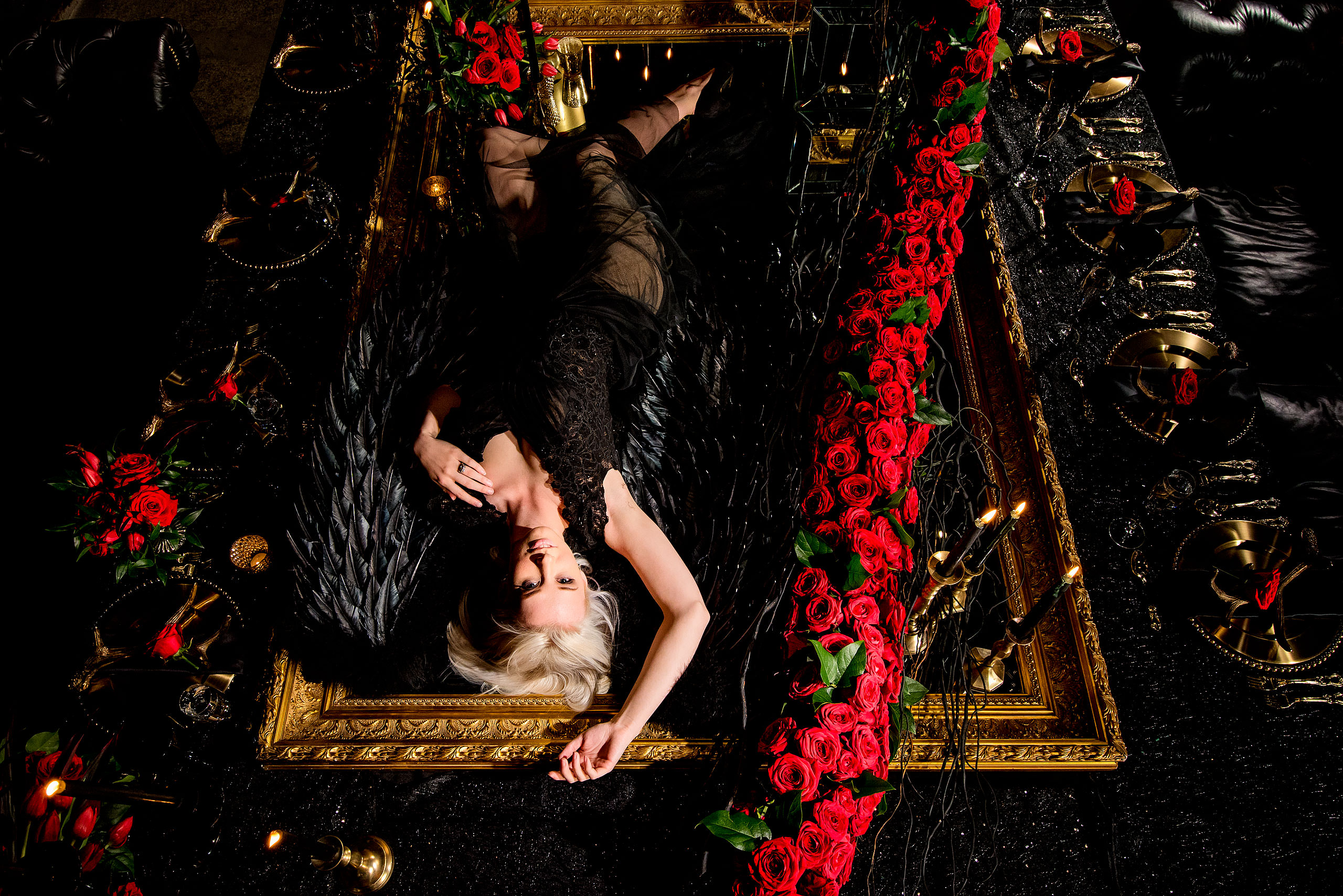 a model wearing a black dress laying down on a mirror beside a string of roses by calgary confetti fashion photographer sean leblanc