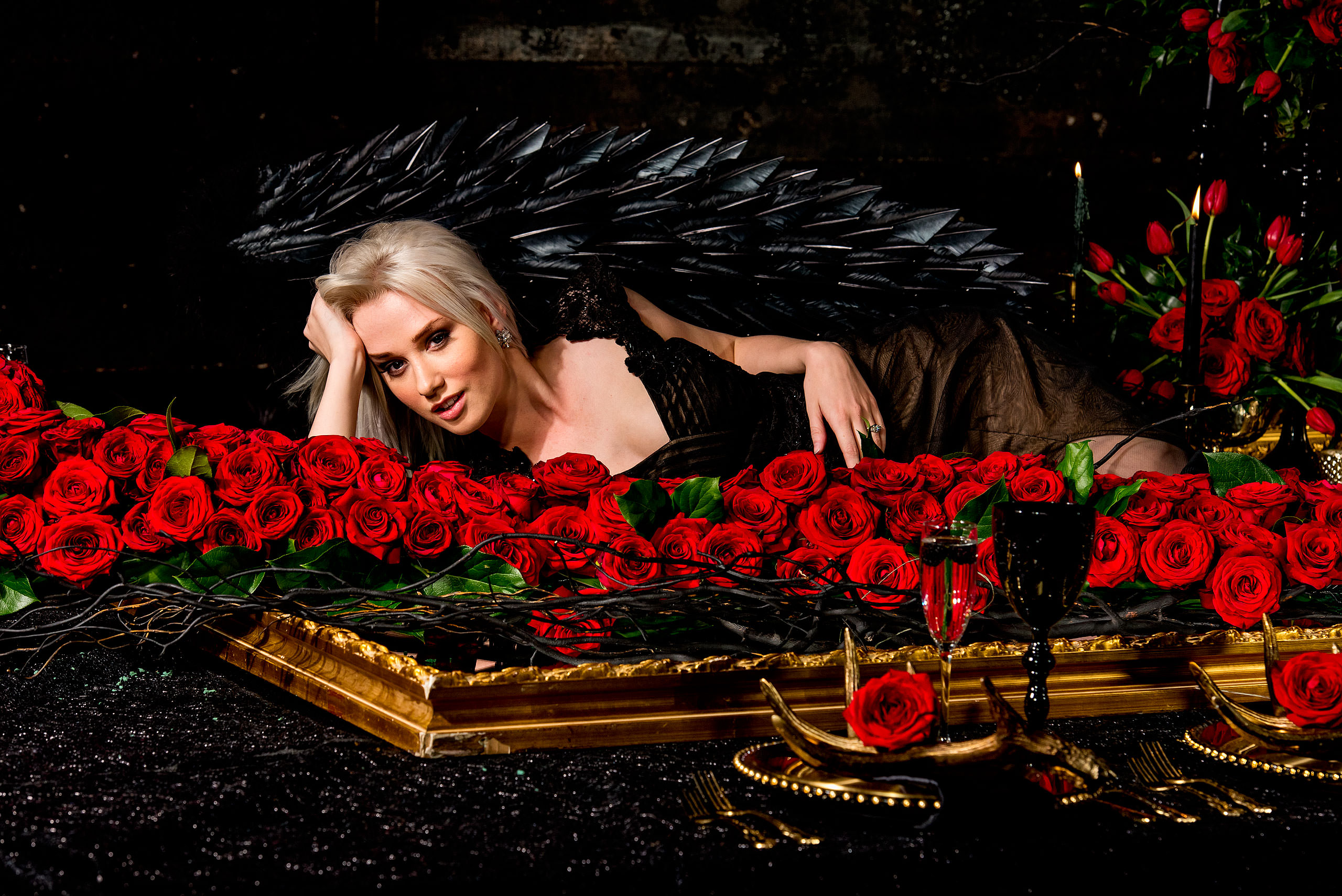 a model wearing wings laying behind roses by calgary confetti fashion photographer sean leblanc