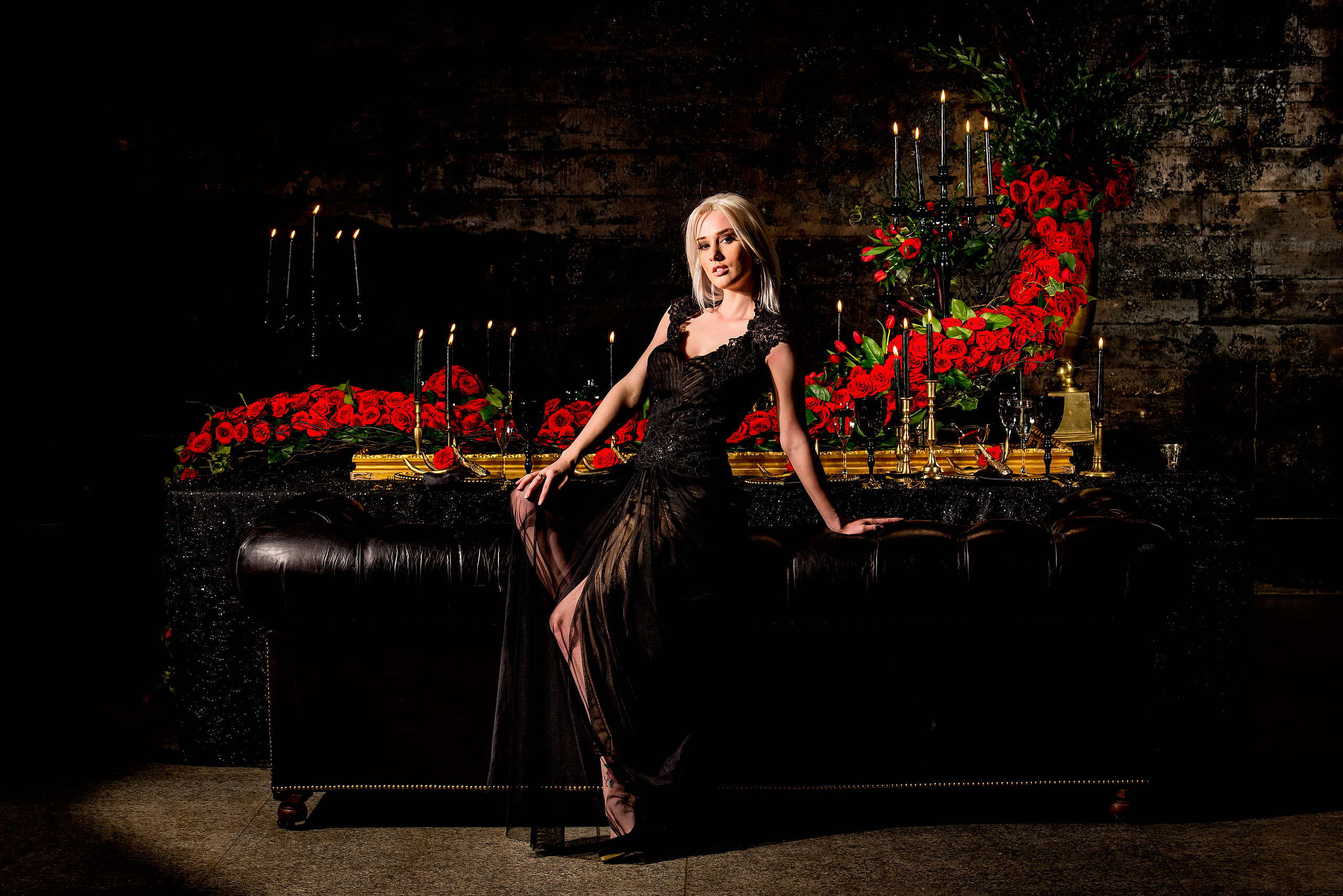 young female model sitting on the edge of a couch in front of a table of roses by calgary confetti fashion photographer sean leblanc