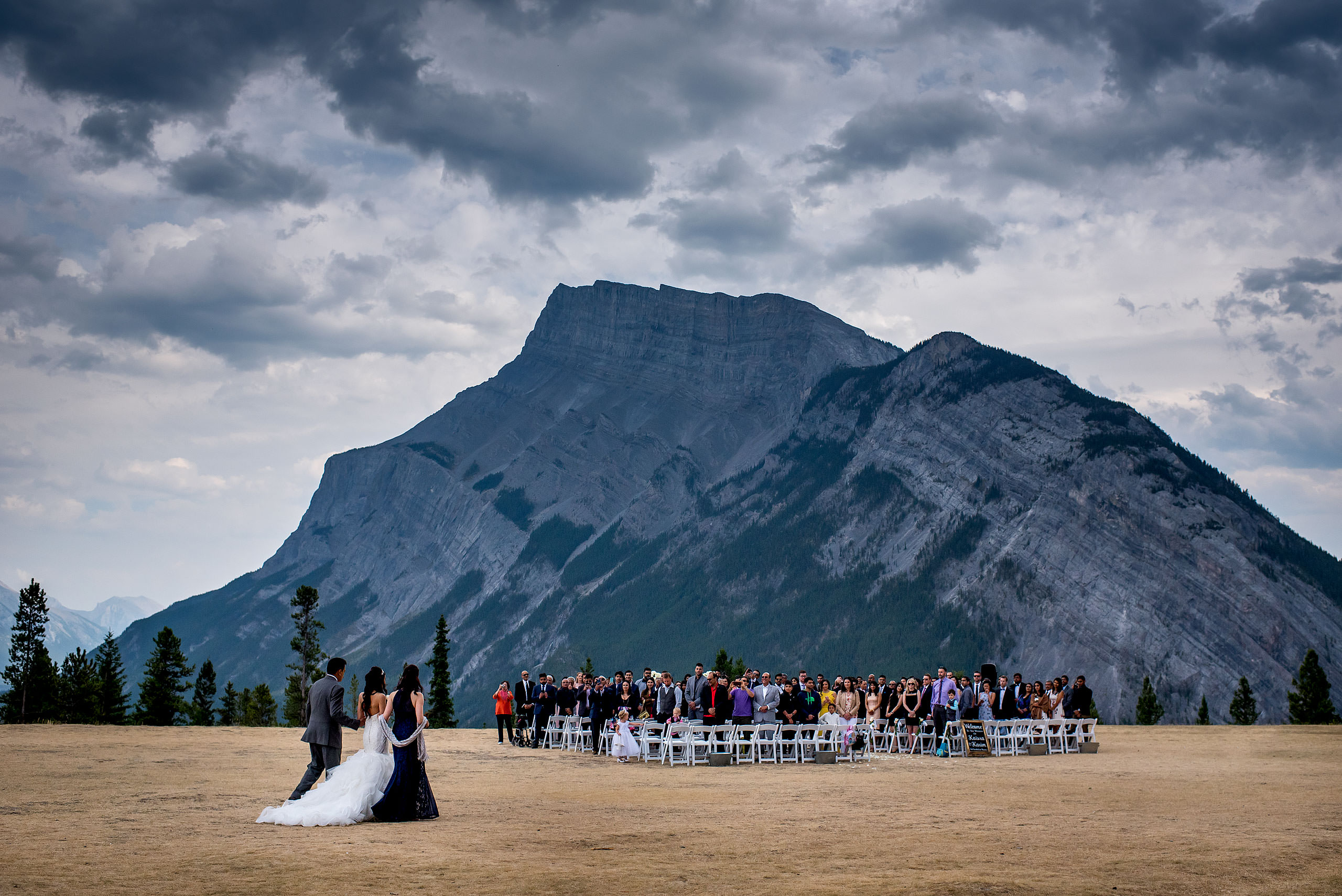 bride walking with parents to ceremony in front of Tunnel Mountain by a Banff wedding Photographer