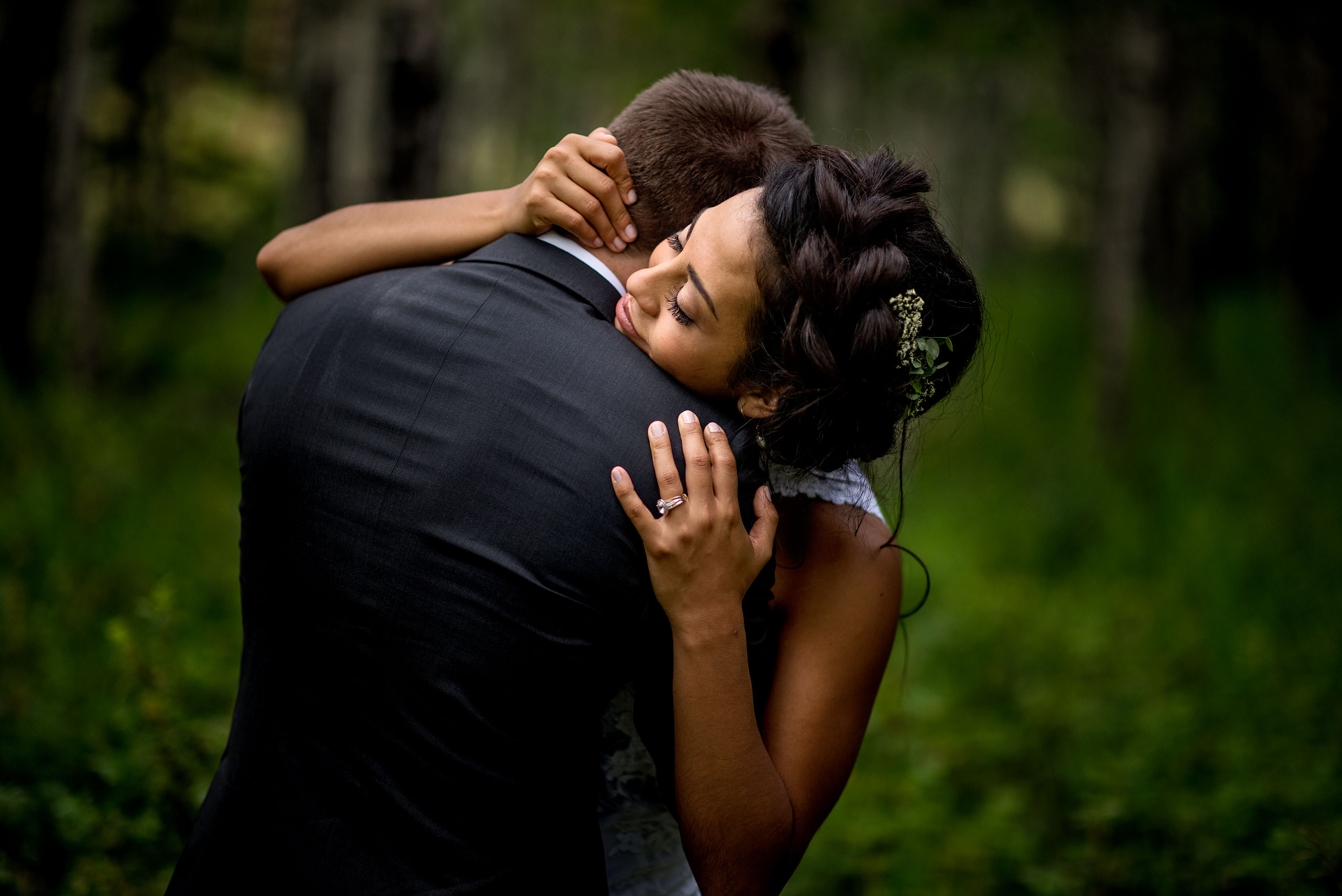 a bride giving her groom a big hug in the forest by calgary wedding photographer sean leblanc