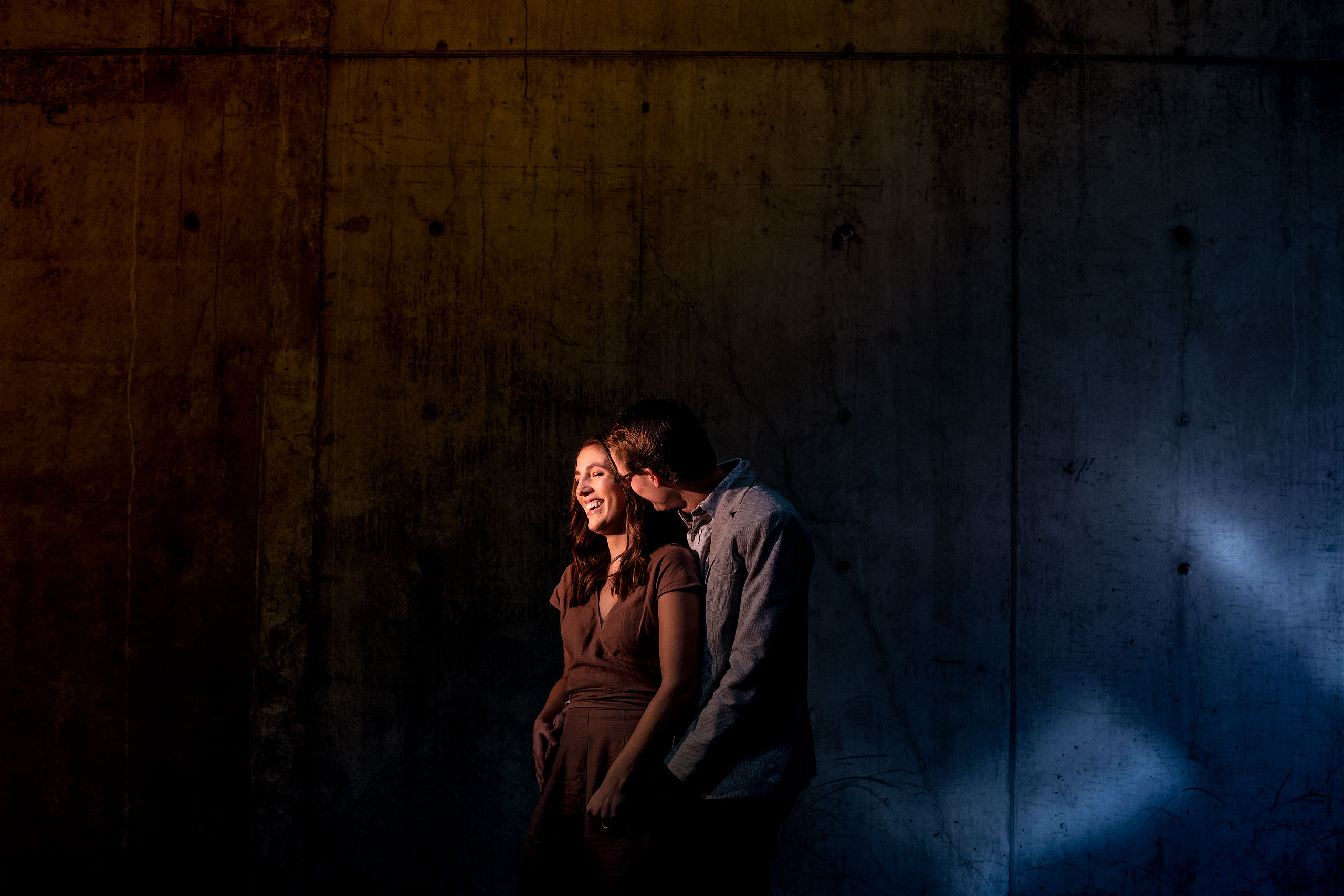 an engaged couple holding each other in front of a concrete wall by calgary engagement photographer sean leblanc
