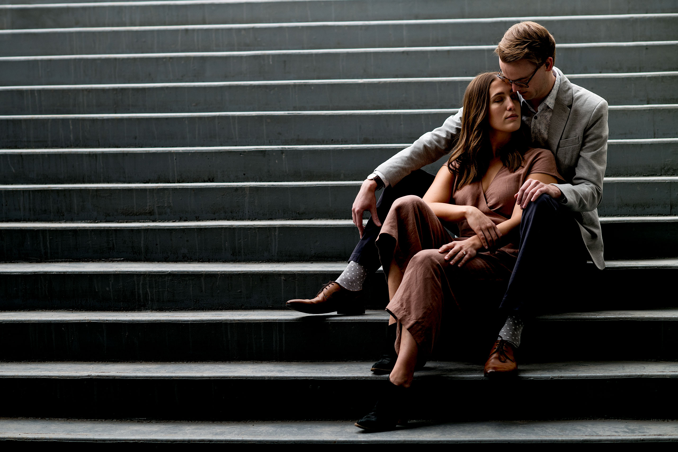 an engaged couple sitting on stairs holding each other by calgary engagement photographer sean leblanc