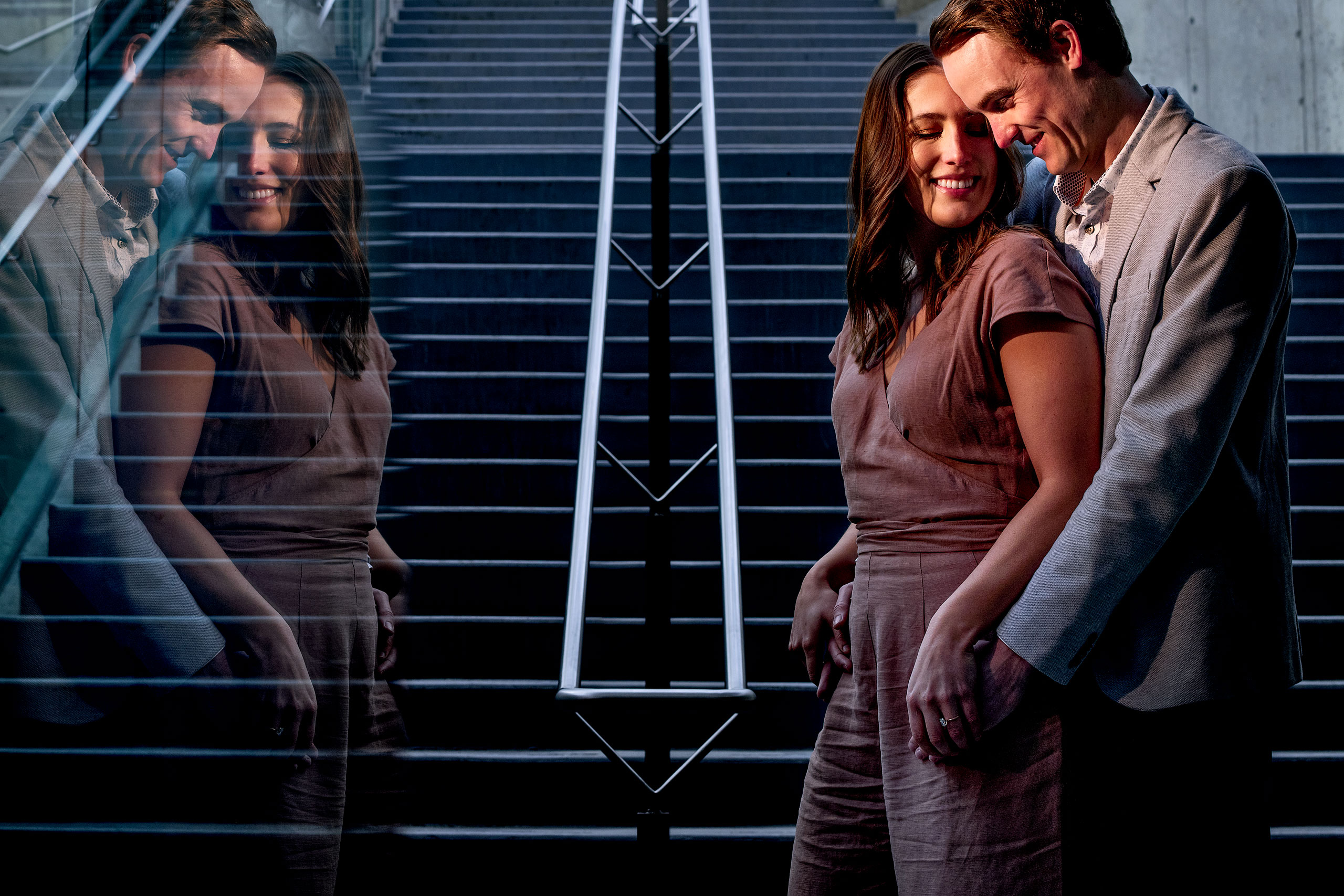 an engaged couple reflected in glass by calgary engagement photographer sean leblanc