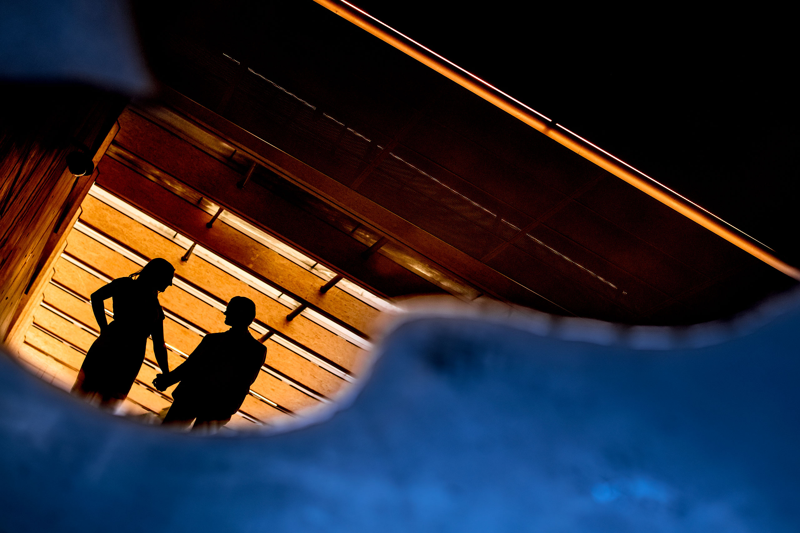 an engaged couple reflected in a puddle by calgary engagement photographer sean leblanc