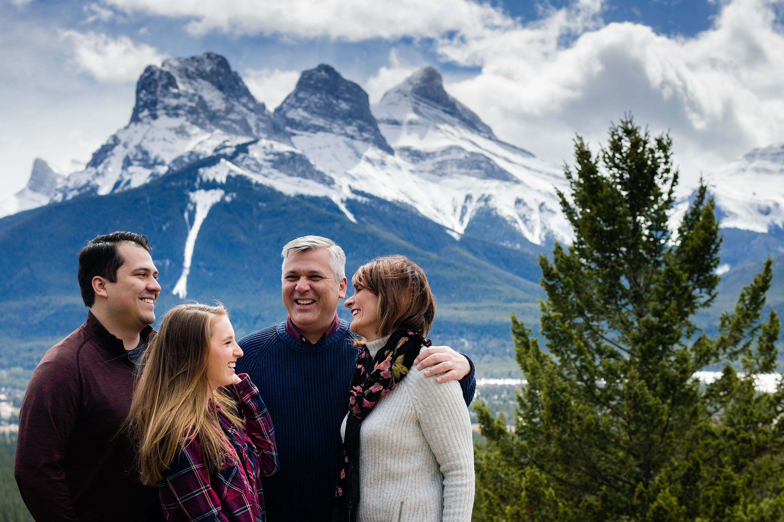 a family of four laughing in front of the three sisters mountains by Canmore Family Photographer Sean LeBlanc