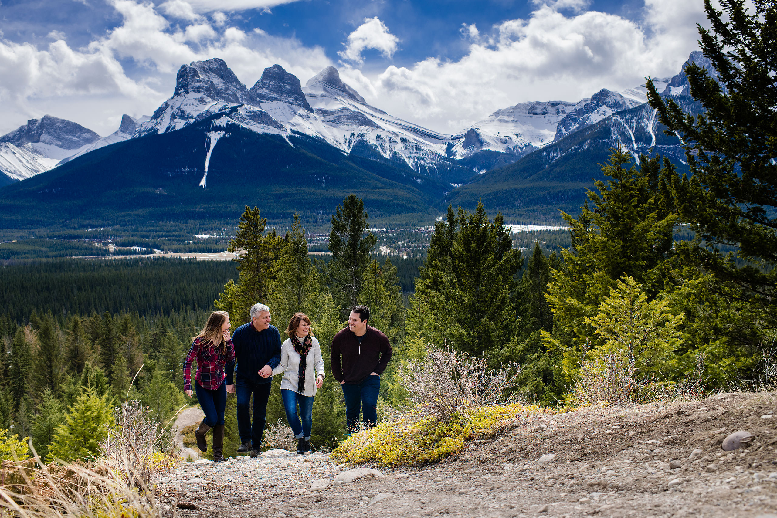 a family of four walking up a mountain together by Canmore Family Photographer Sean LeBlanc
