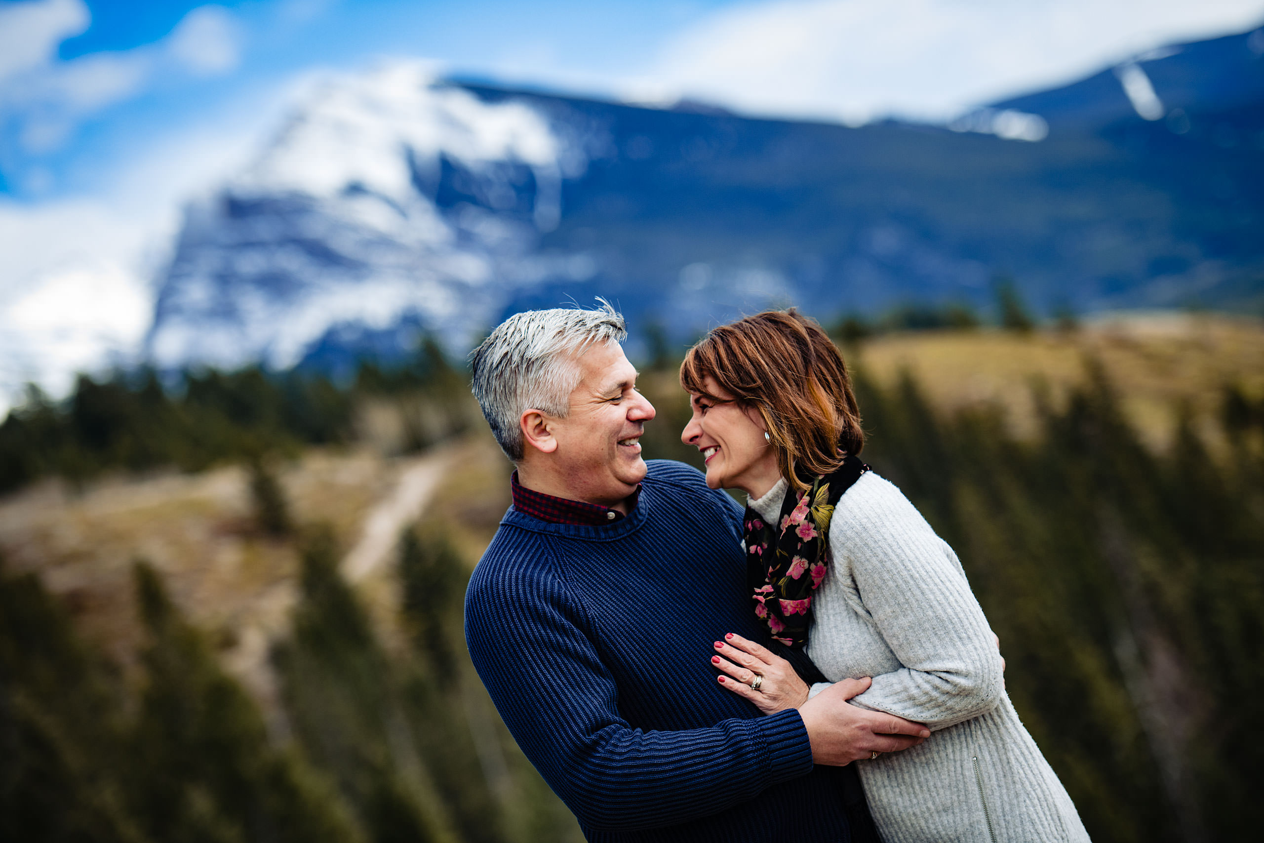 a husband and wife embracing each other with a mountain in the background by Canmore Family Photographer Sean LeBlanc