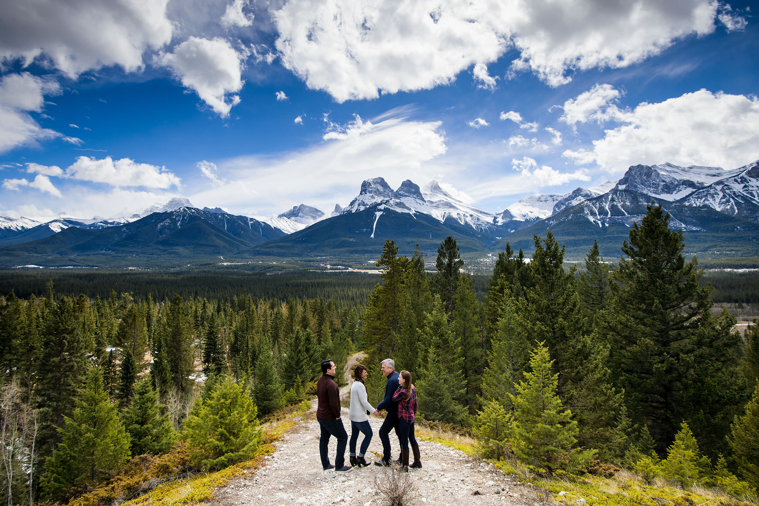 a family of four standing on a pathway smiling at each other by Canmore Family Photographer Sean LeBlanc