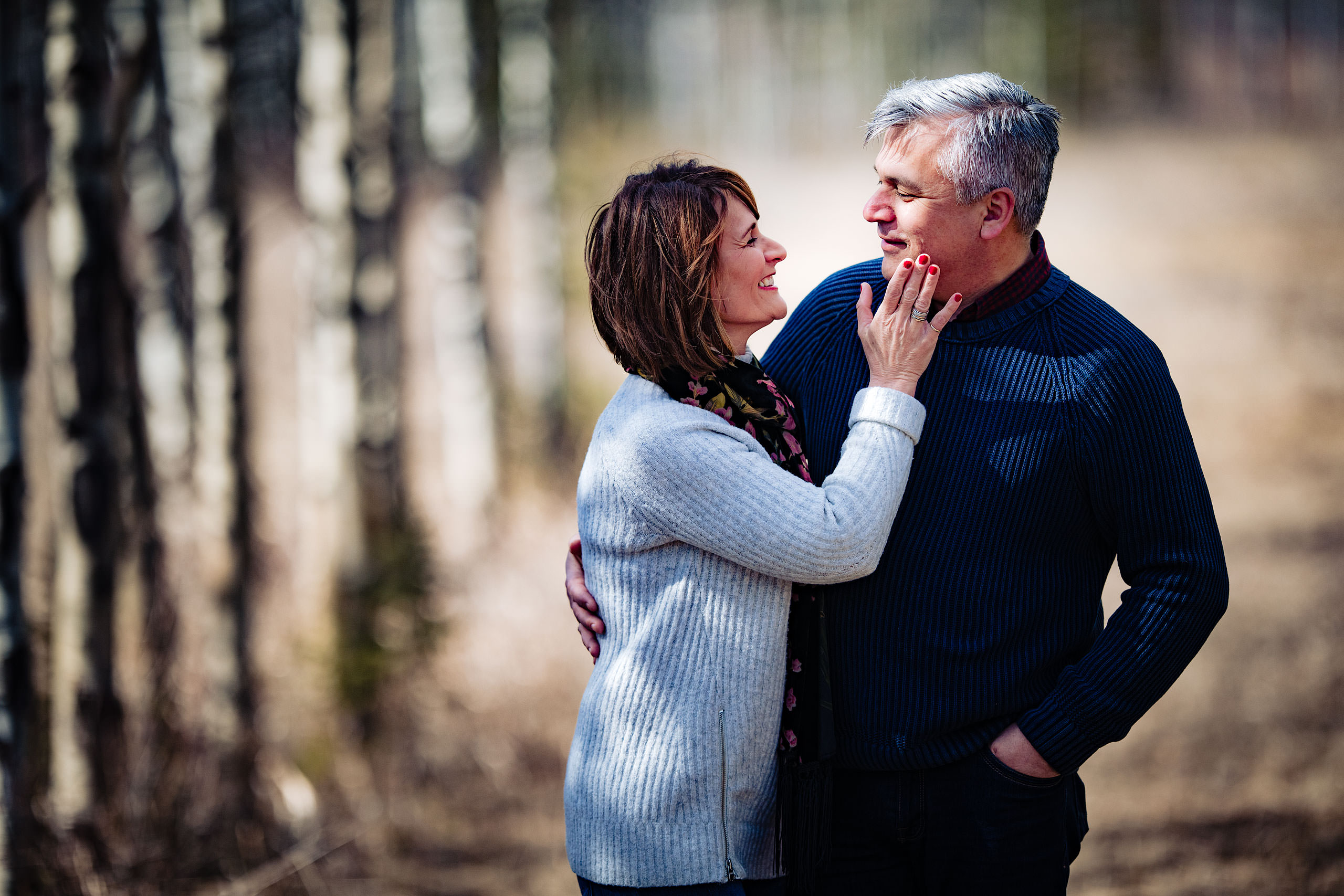 a wife holding the cheek of her husband by Canmore Family Photographer Sean LeBlanc