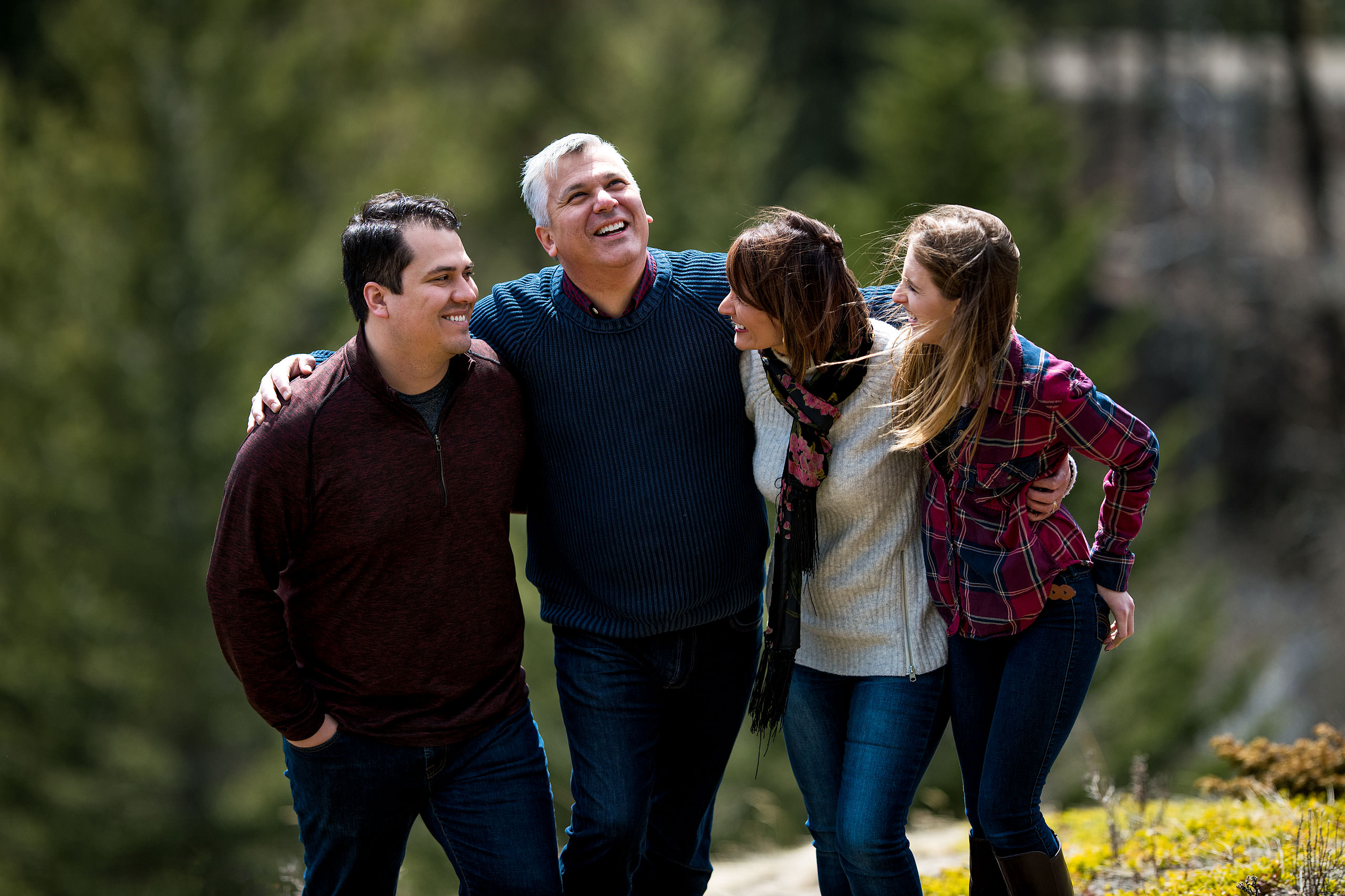 a family of four with their arms around each other laughing by Canmore Family Photographer Sean LeBlanc