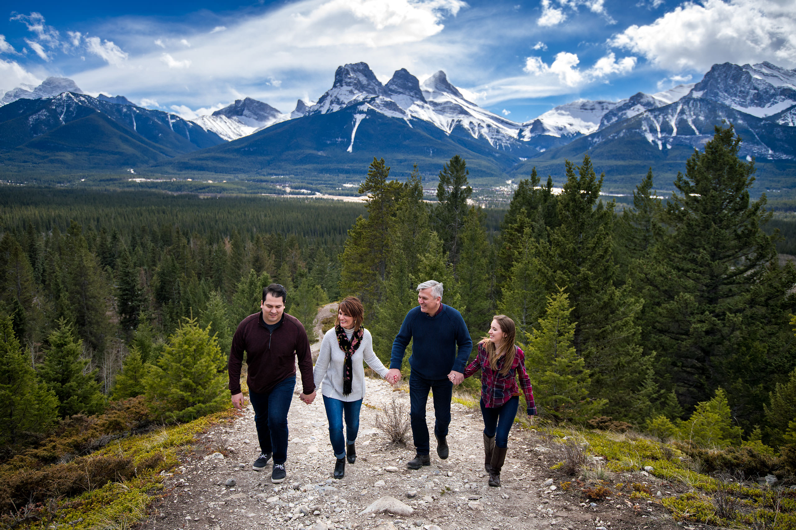 a family holding hands walking up a mountain by Canmore Family Photographer Sean LeBlanc