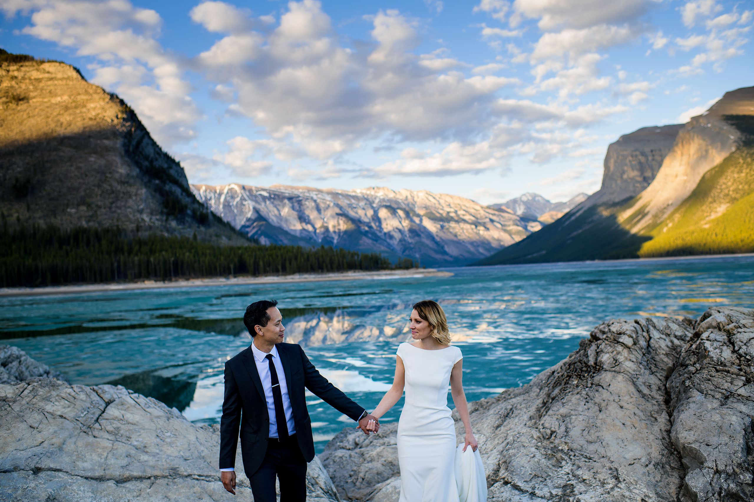 a groom and bride walking up from a lake surrounded by mountains by top Banff photographer sean leblanc
