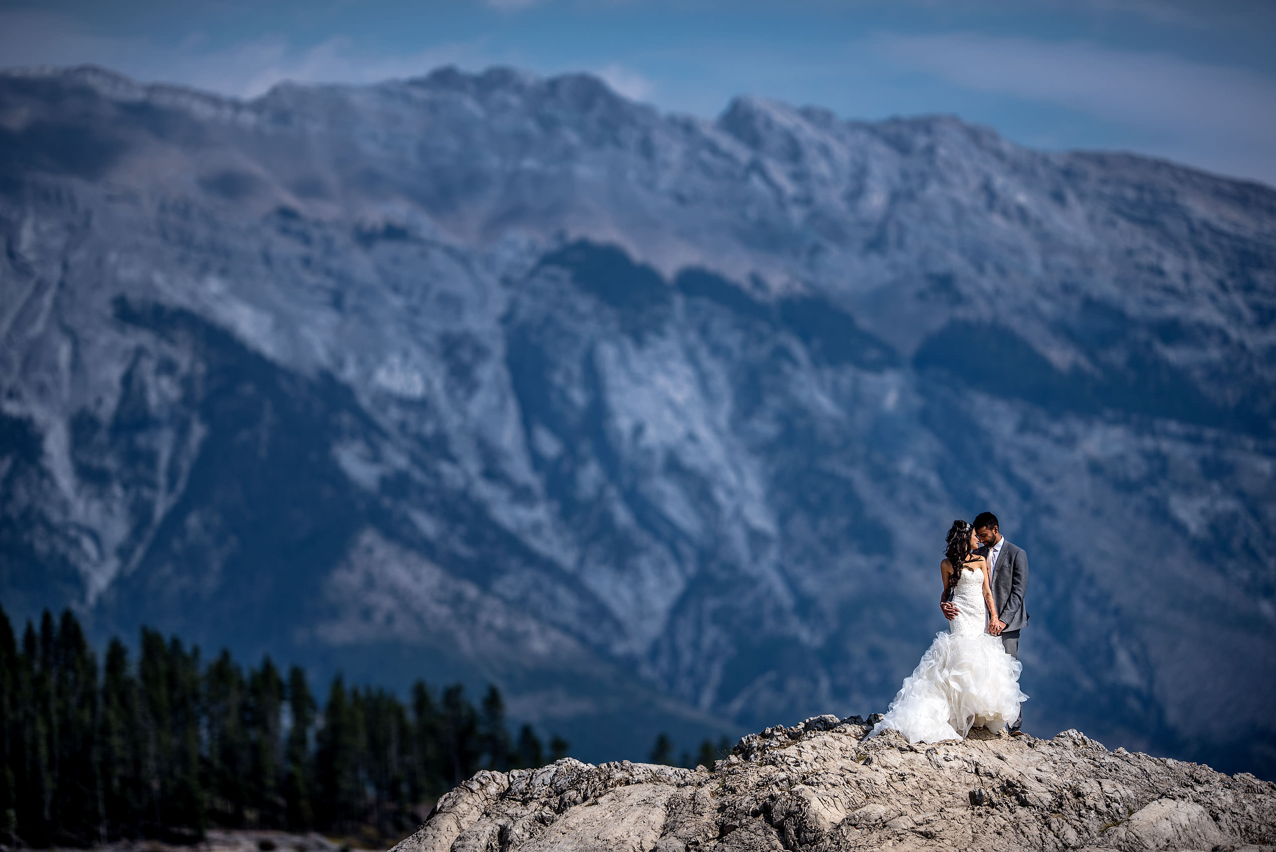 a bride and groom embracing on top of a rock with a mountain in the background by Calgary Banff Wedding Photographer Sean LeBlanc