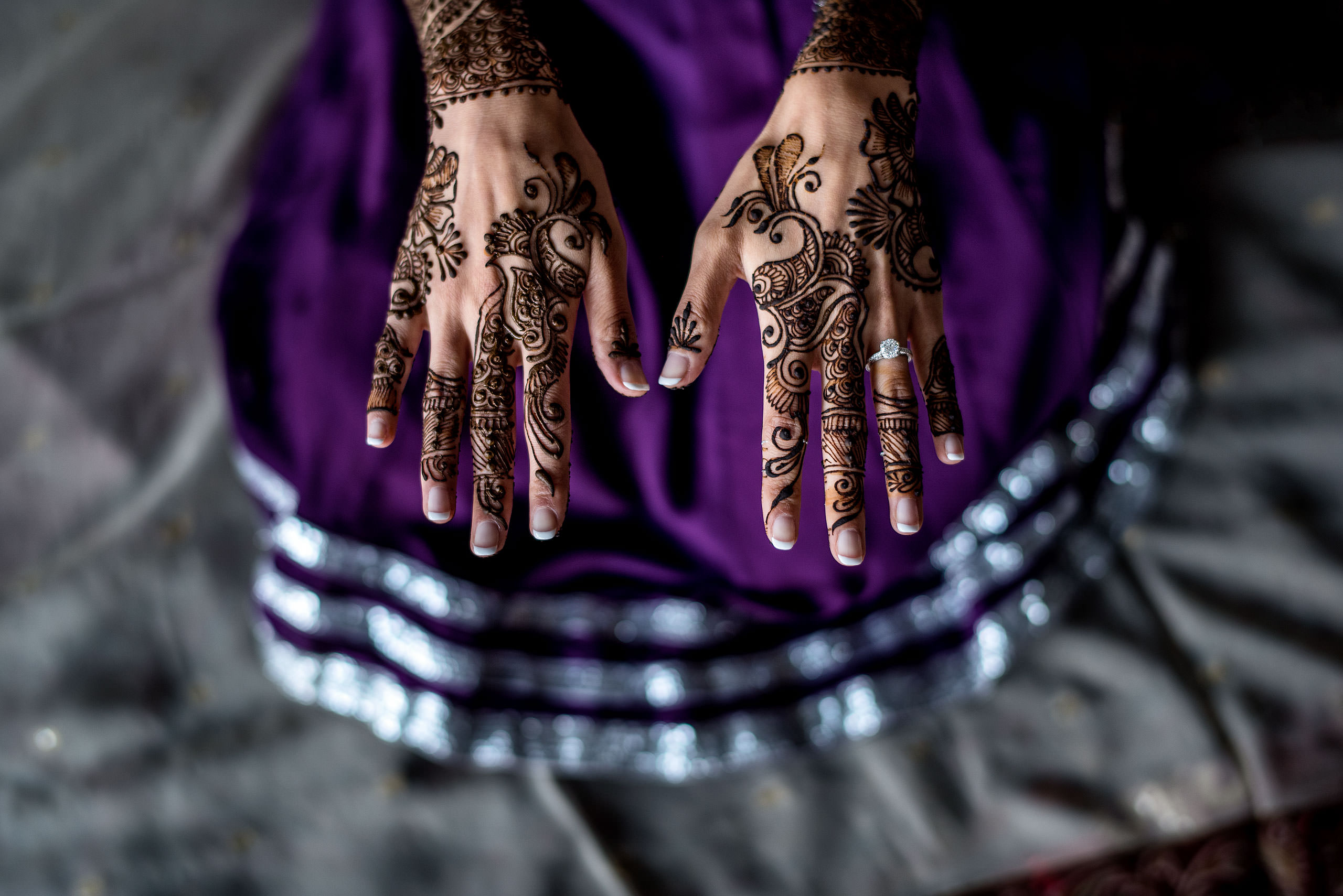 two hands above a purple dress with a wedding ring by Calgary Banff Wedding Photographer Sean LeBlanc