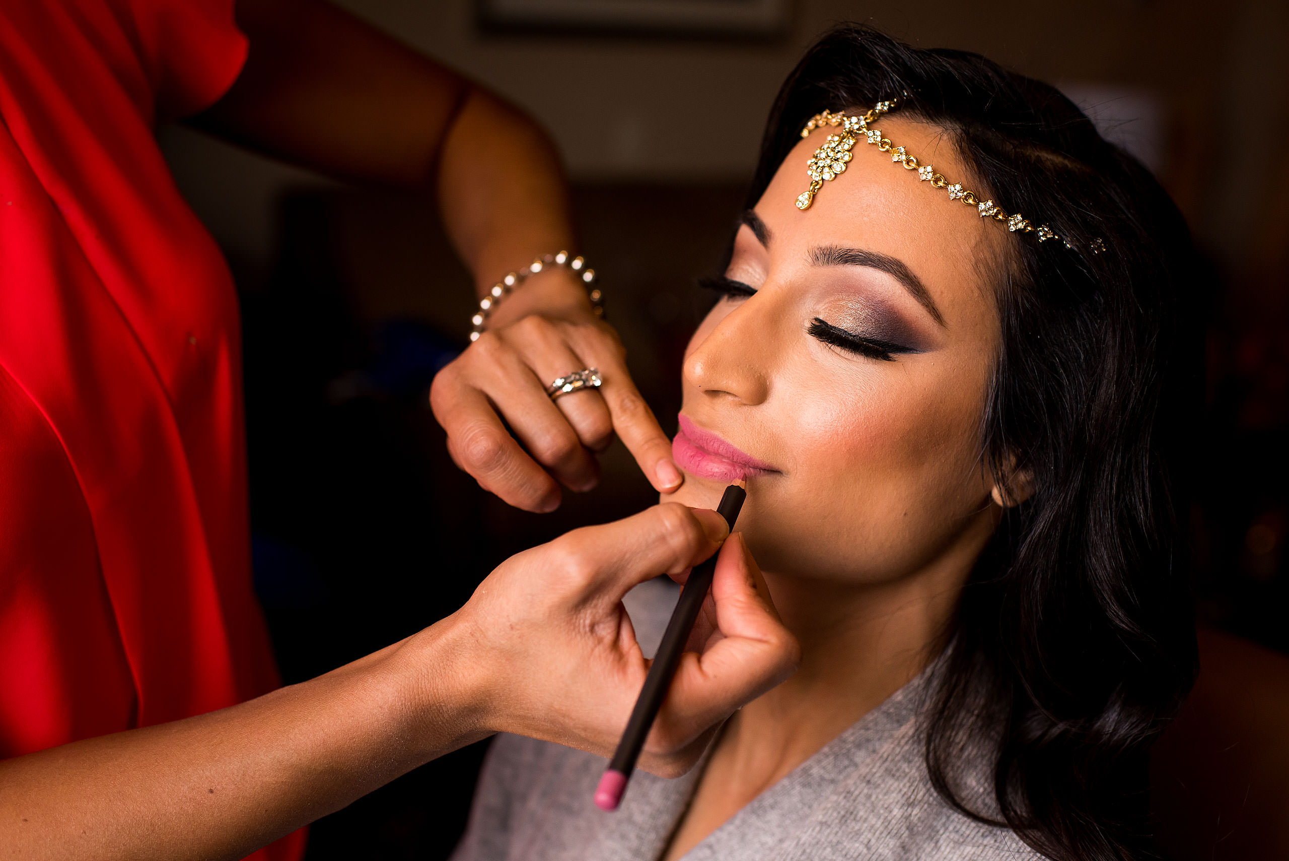 an indian bride having lip stick applied while she gets ready for her wedding day by Calgary Banff Wedding Photographer Sean LeBlanc