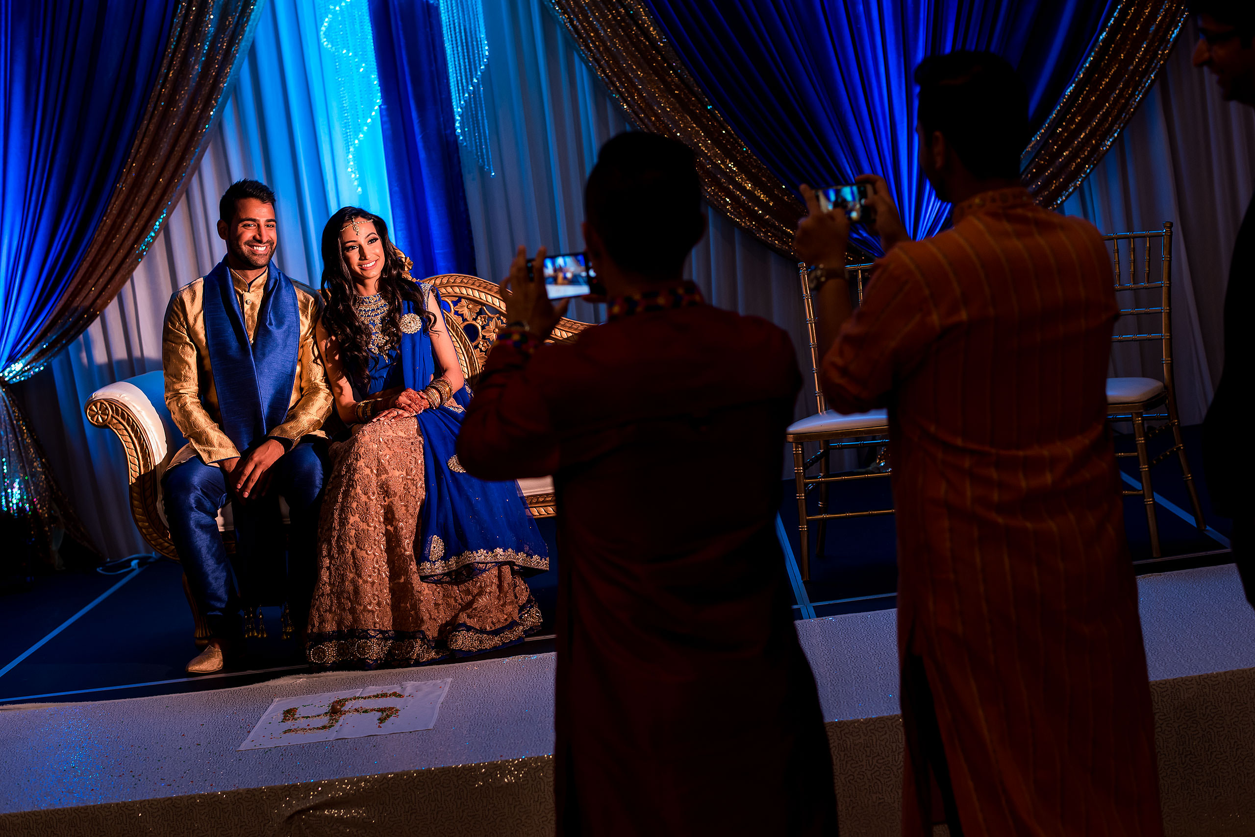 an indian bride and groom sitting on chairs having their photo taken by wedding guests by Calgary Banff Wedding Photographer Sean LeBlanc
