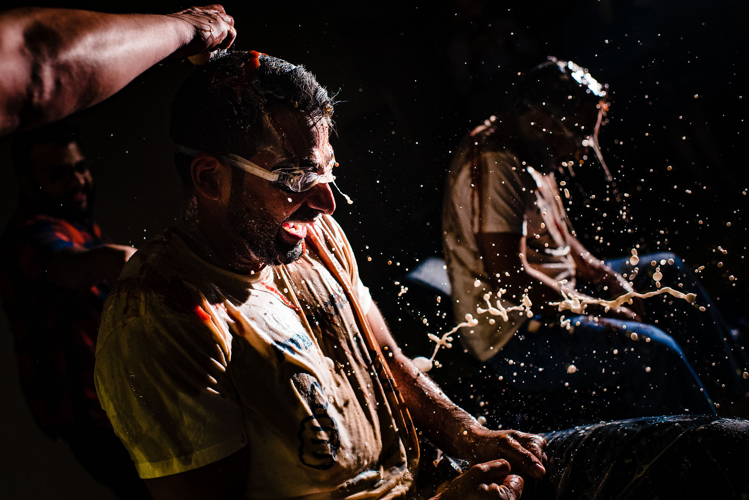 two Indian men getting milk poured on them by Calgary Banff Wedding Photographer Sean LeBlanc