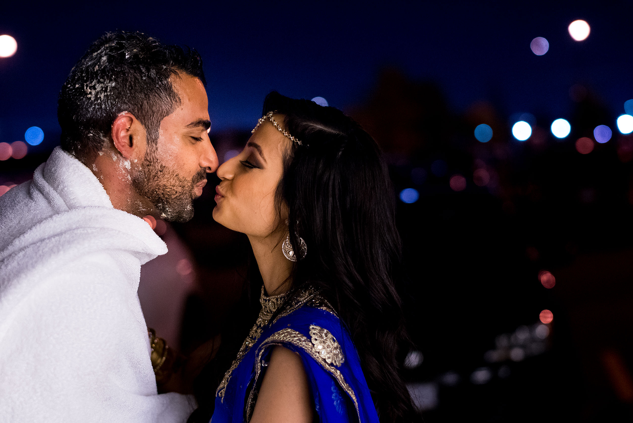 an indian bride and groom kissing in the night by Calgary Banff Wedding Photographer Sean LeBlanc
