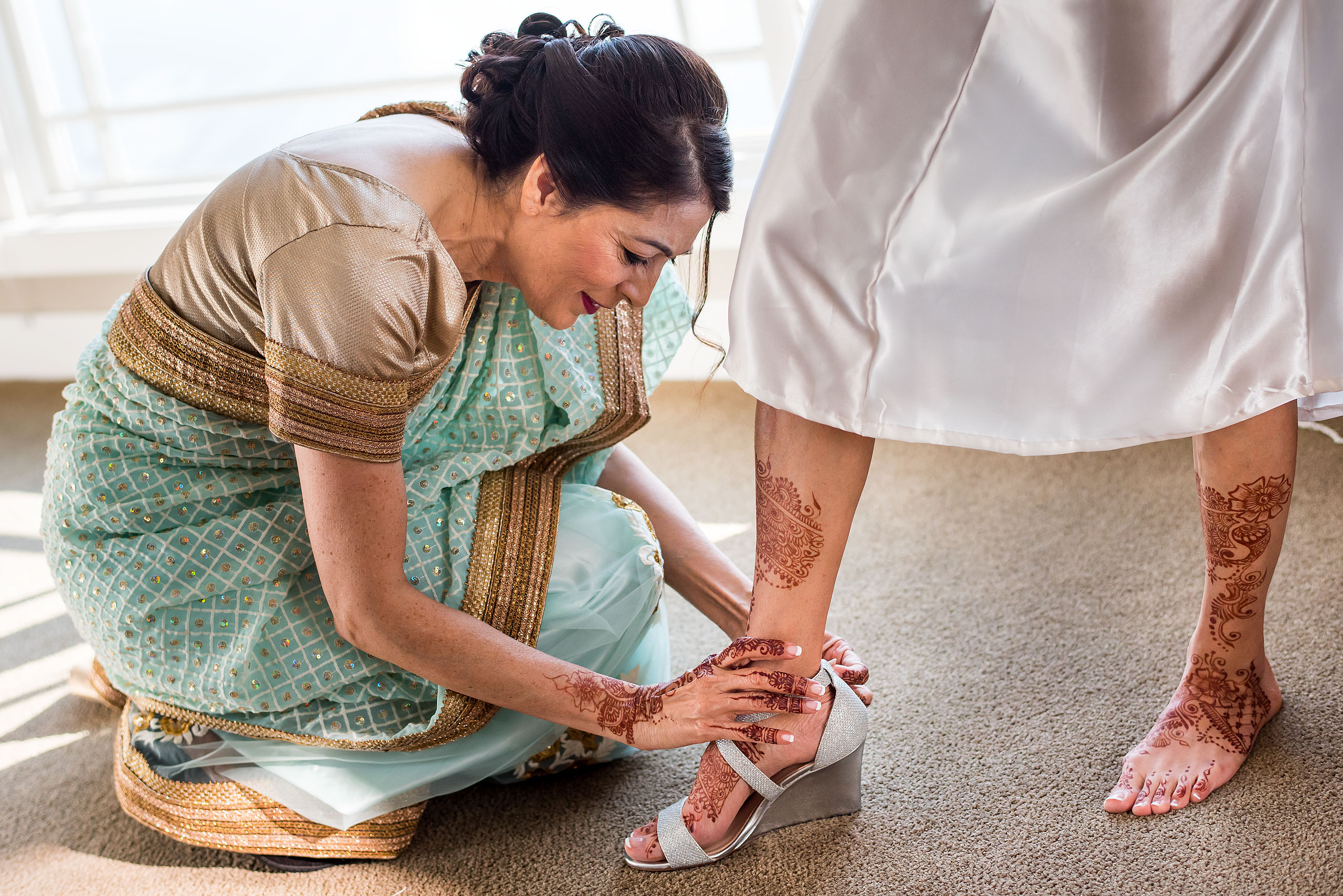 an Indian mom helping put on her daughters wedding shoes by Calgary Banff Wedding Photographer Sean LeBlanc