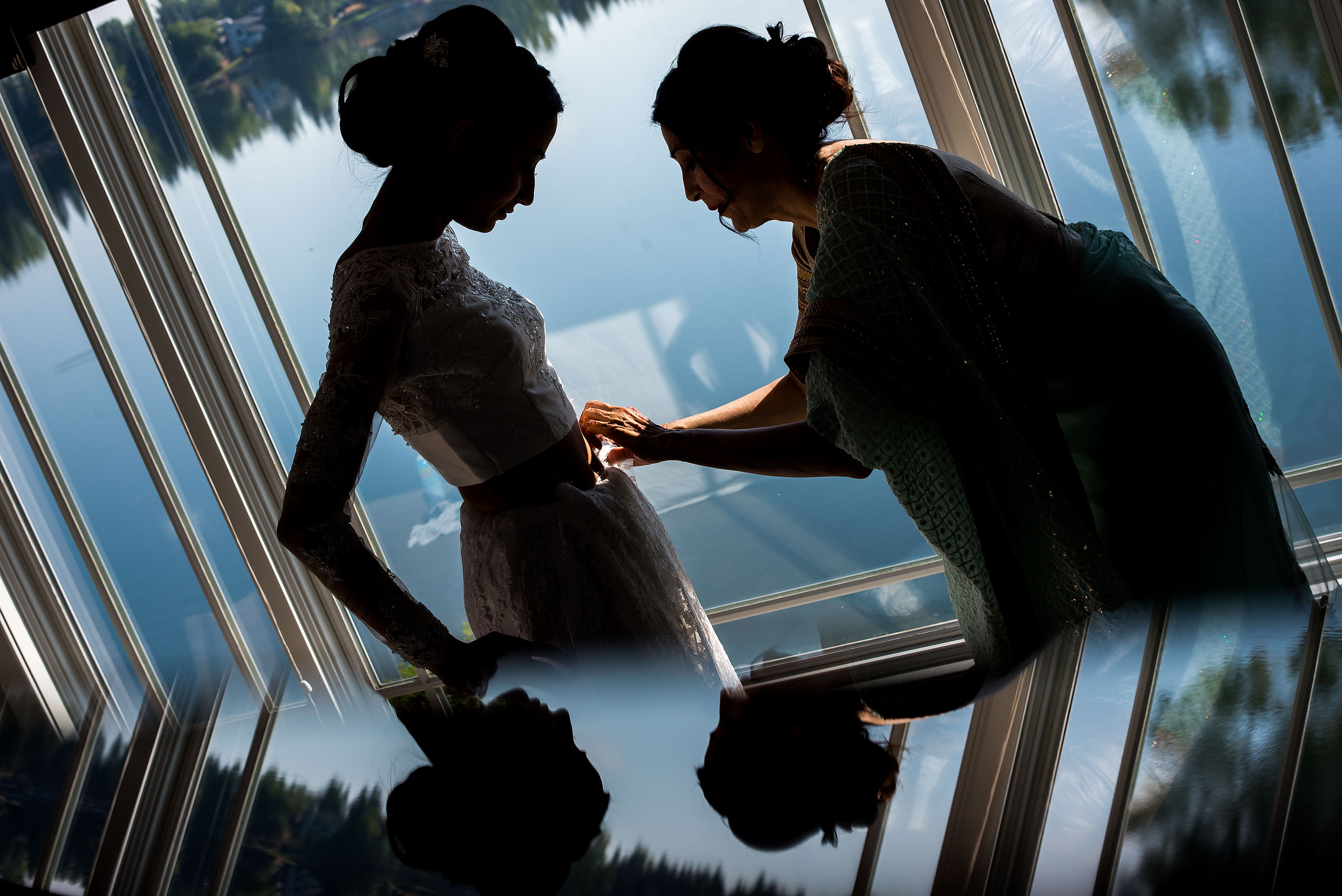 a silhouette of a mom helping her daughter with her wedding dress by Calgary Banff Wedding Photographer Sean LeBlanc
