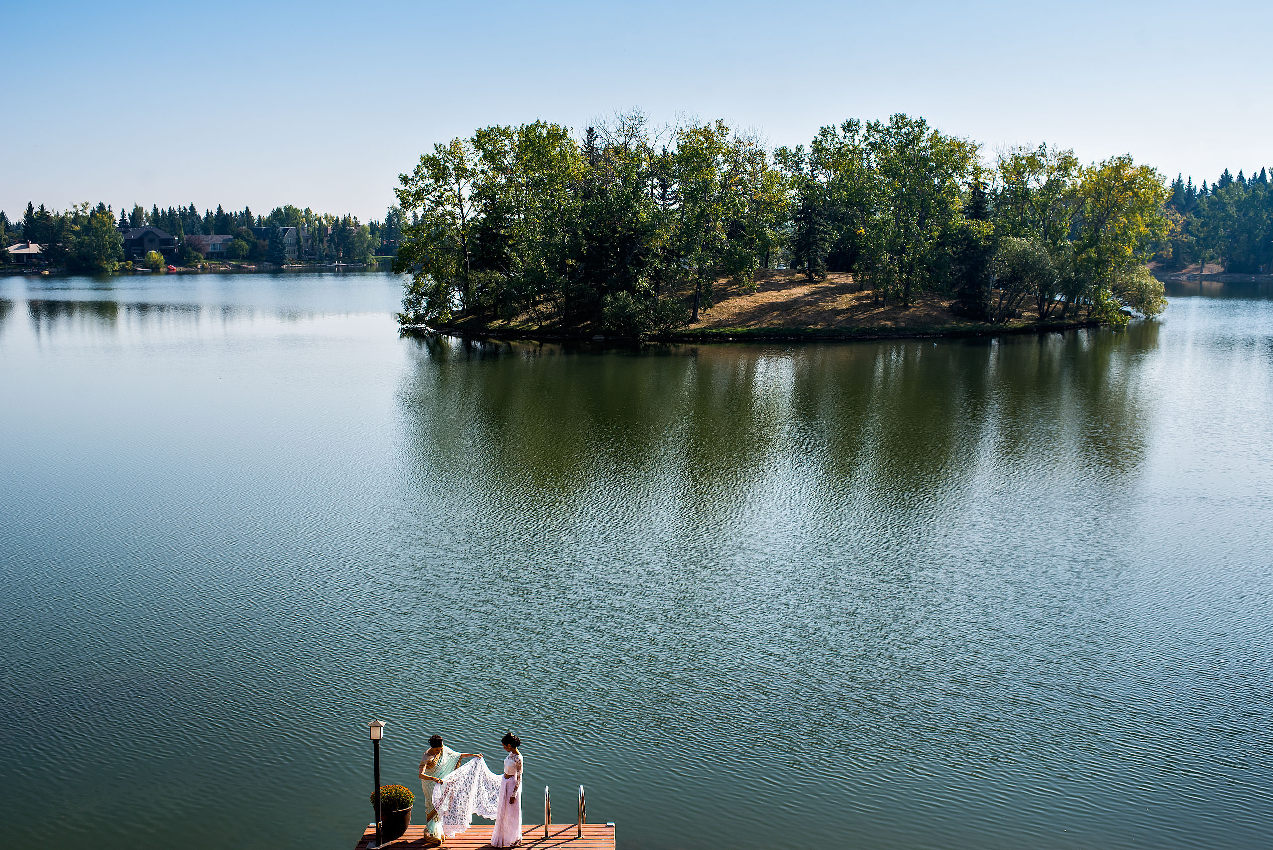 a mom and a daughter on a dock in front of a lake by Calgary Banff Wedding Photographer Sean LeBlanc