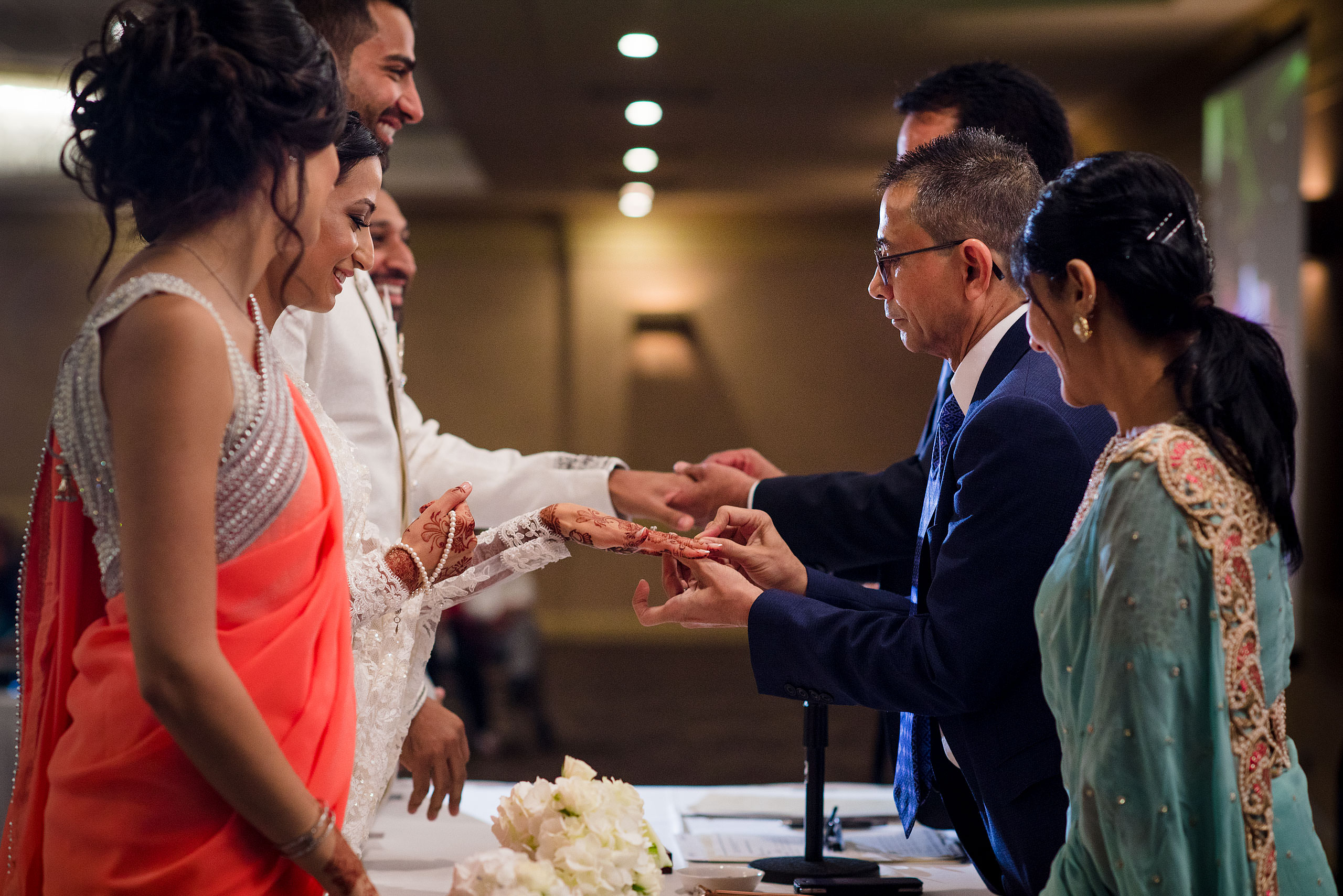 a group of people exchanging rings by Calgary Banff Wedding Photographer Sean LeBlanc