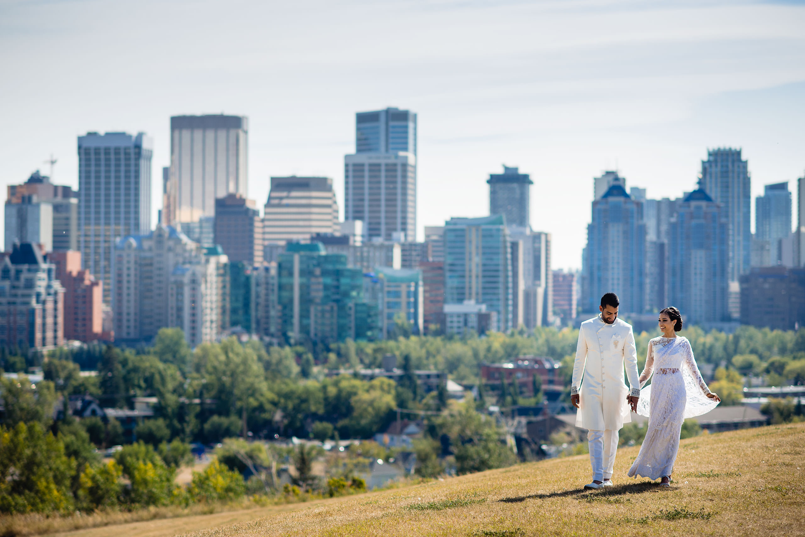 an Indian bride and groom walking on a hill in front of downtown Calgary by Calgary Banff Wedding Photographer Sean LeBlanc