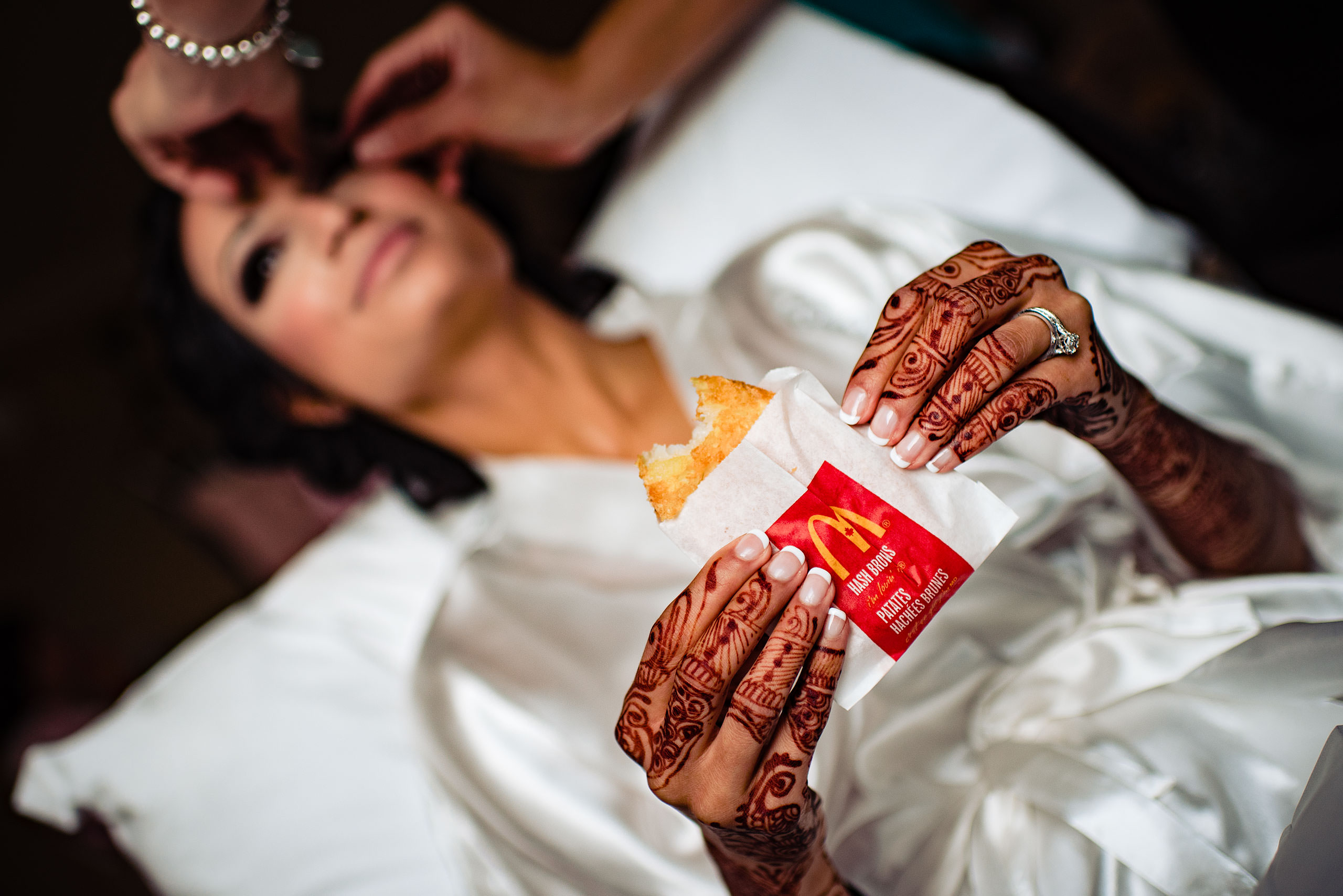 a bride eating a hashbrown from Mcdonalds by Calgary Banff Wedding Photographer Sean LeBlanc