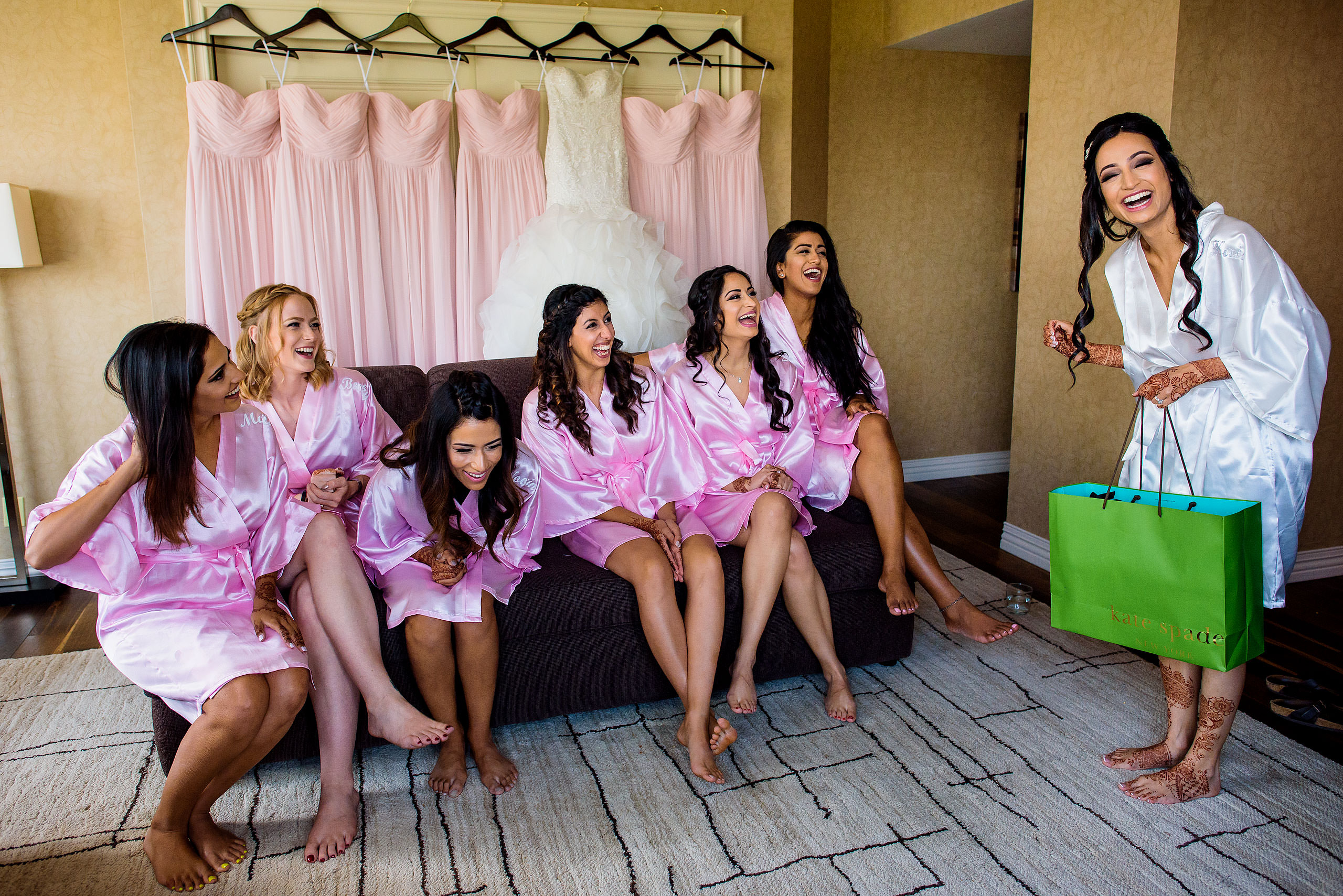 a group of bridesmaids wearing pink coats by Calgary Banff Wedding Photographer Sean LeBlanc