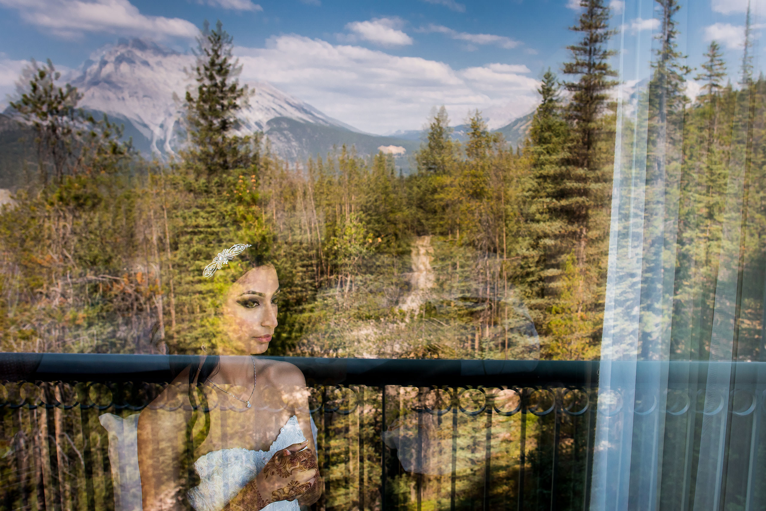 a bride looking out a window by Calgary Banff Wedding Photographer Sean LeBlanc