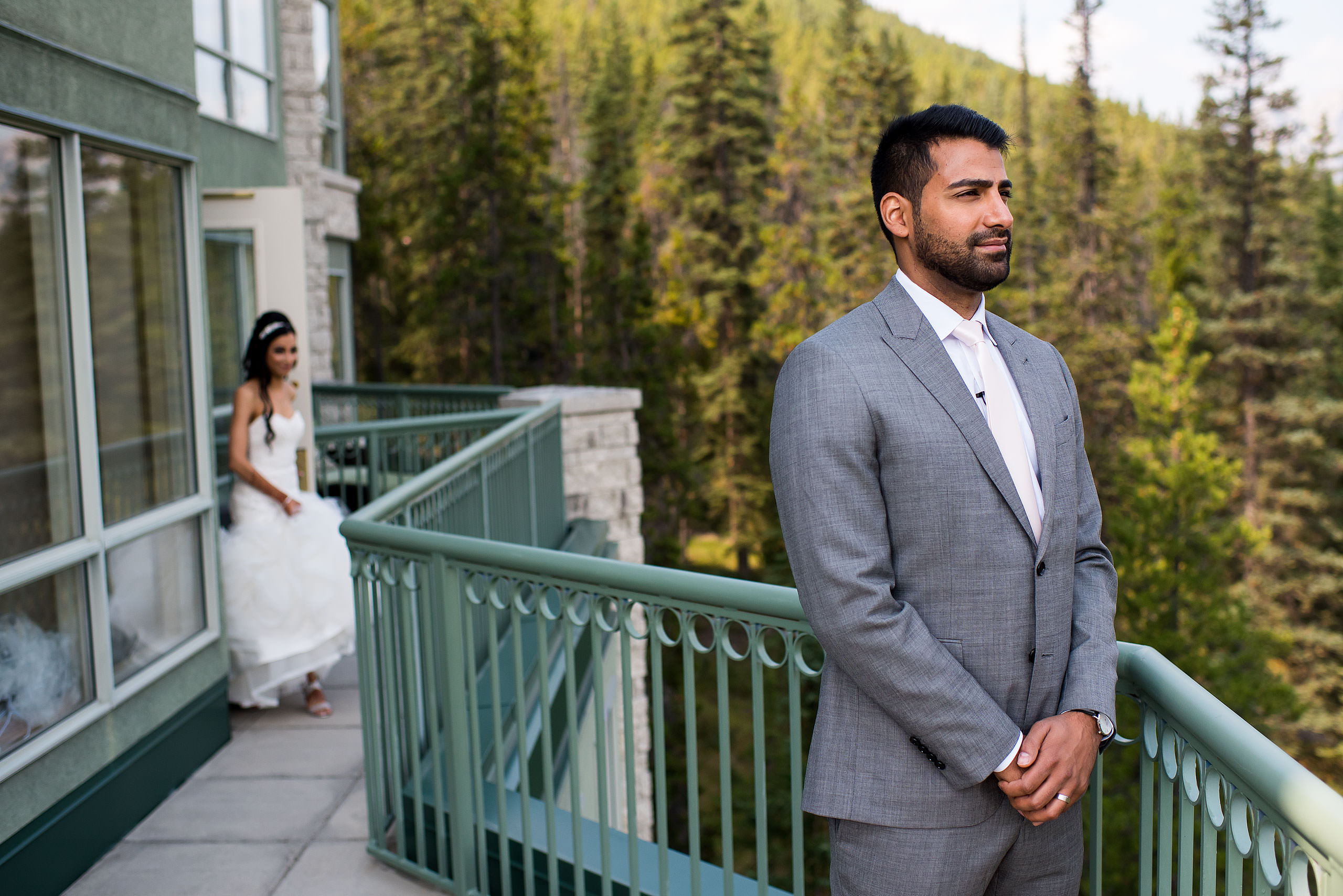 a groom waiting on a balcony at the Rimrock hotel for his bride by Calgary Banff Wedding Photographer Sean LeBlanc