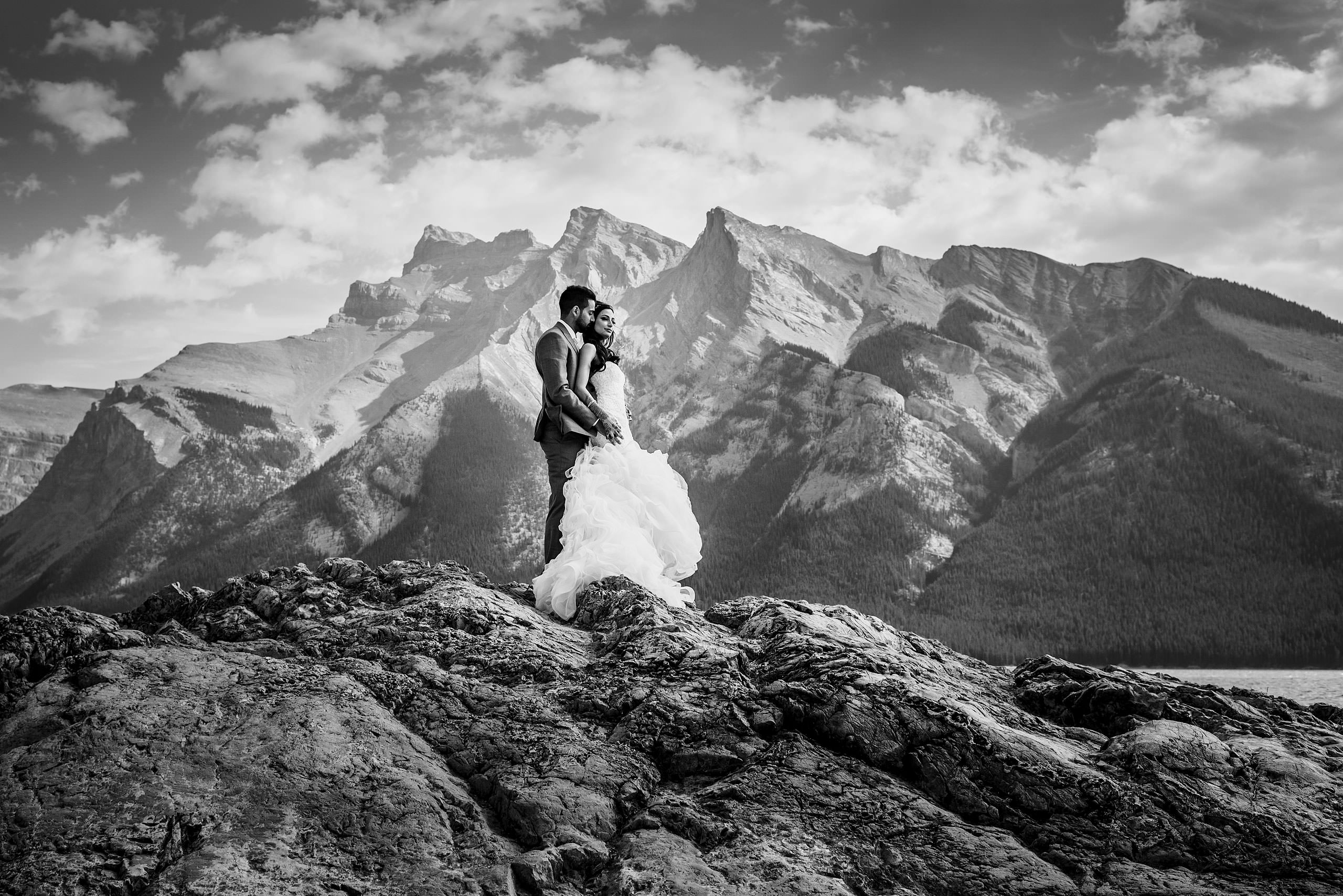 a bride and groom embracing on top of a mountain by Calgary Banff Wedding Photographer Sean LeBlanc
