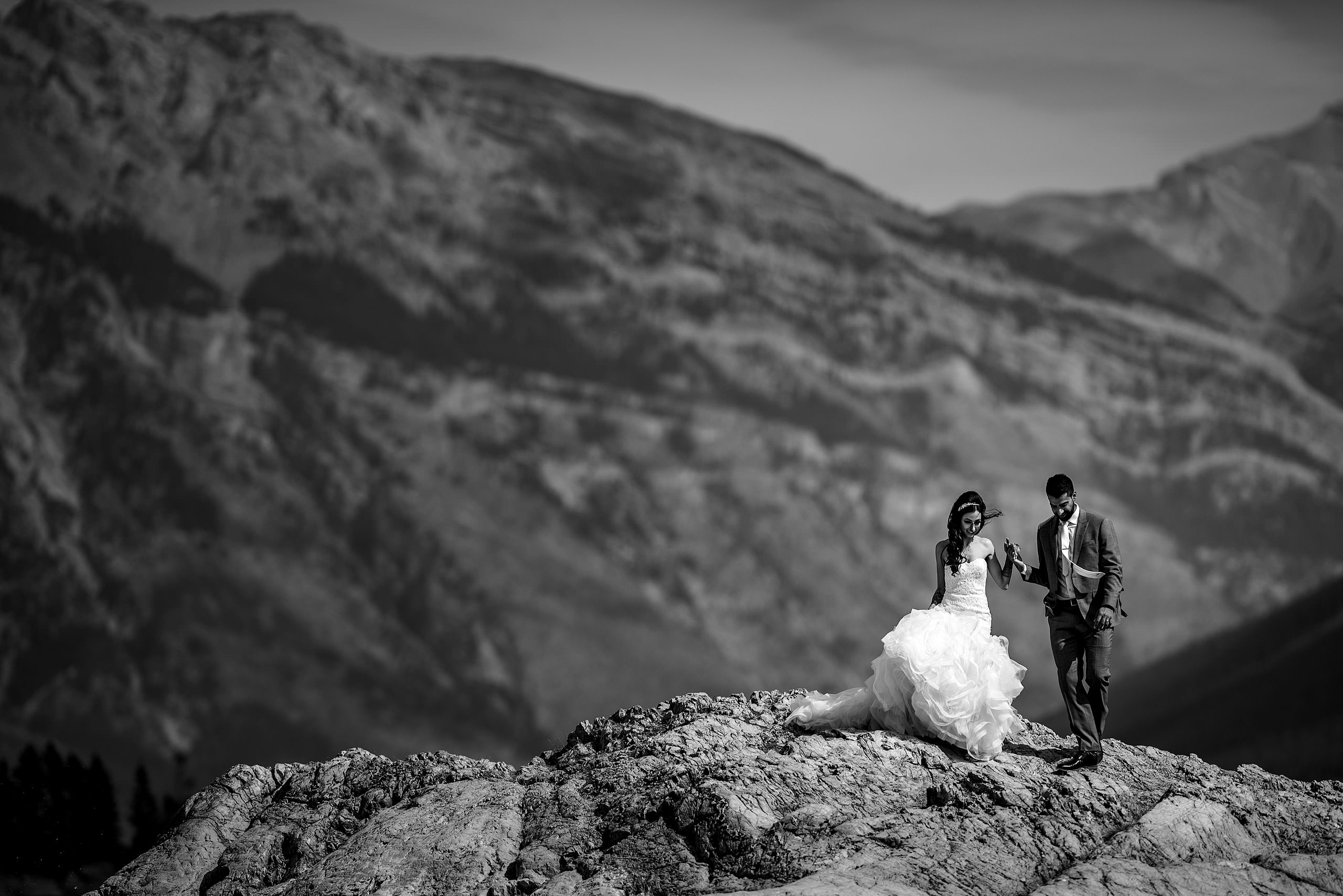 a bride and groom walking down from a rock by Calgary Banff Wedding Photographer Sean LeBlanc