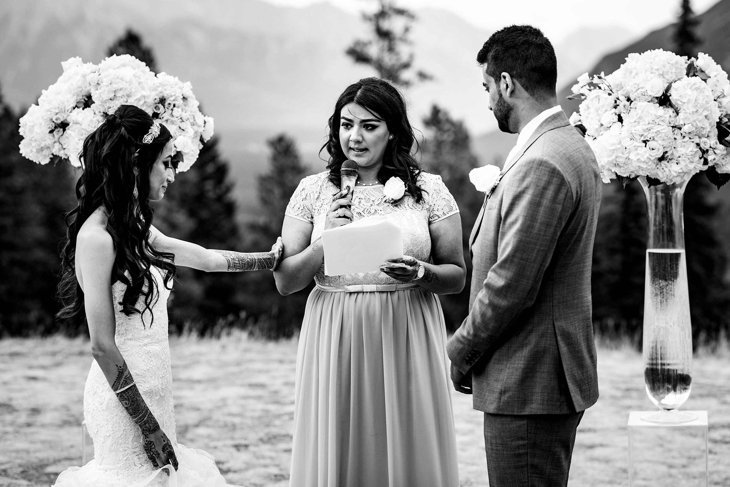 an Indian women speaking to a bride and groom by Calgary Banff Wedding Photographer Sean LeBlanc