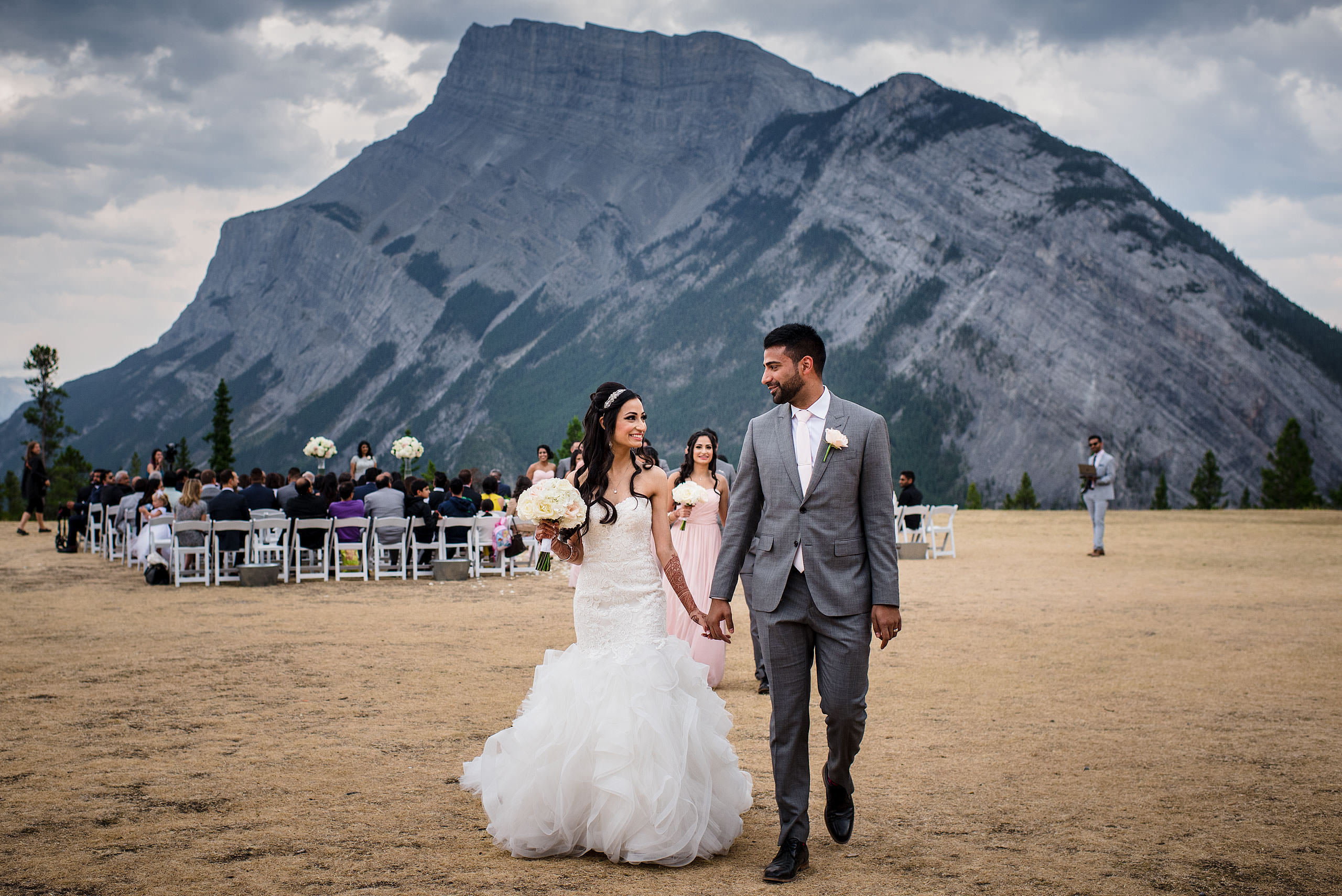 a bride and groom walking from their wedding ceremony by Calgary Banff Wedding Photographer Sean LeBlanc