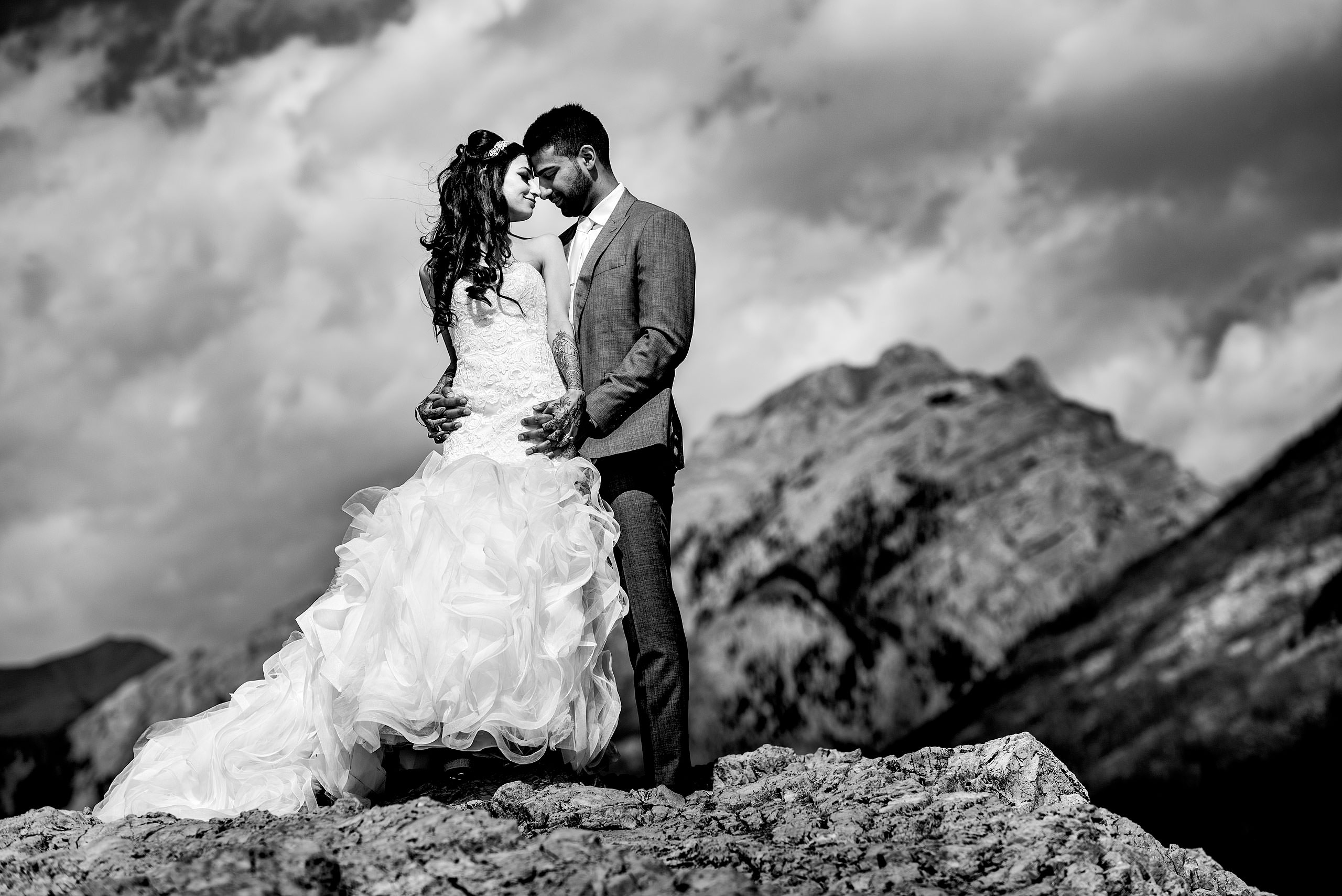a bride and groom embracing on a mountain top by Calgary Banff Wedding Photographer Sean LeBlanc