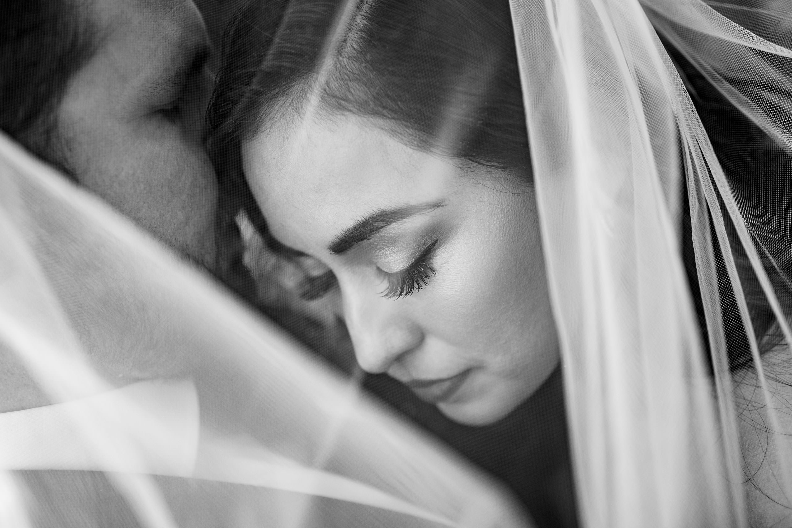 a bride and groom embracing with a veil over their heads by top calgary wedding photographer sean leblanc