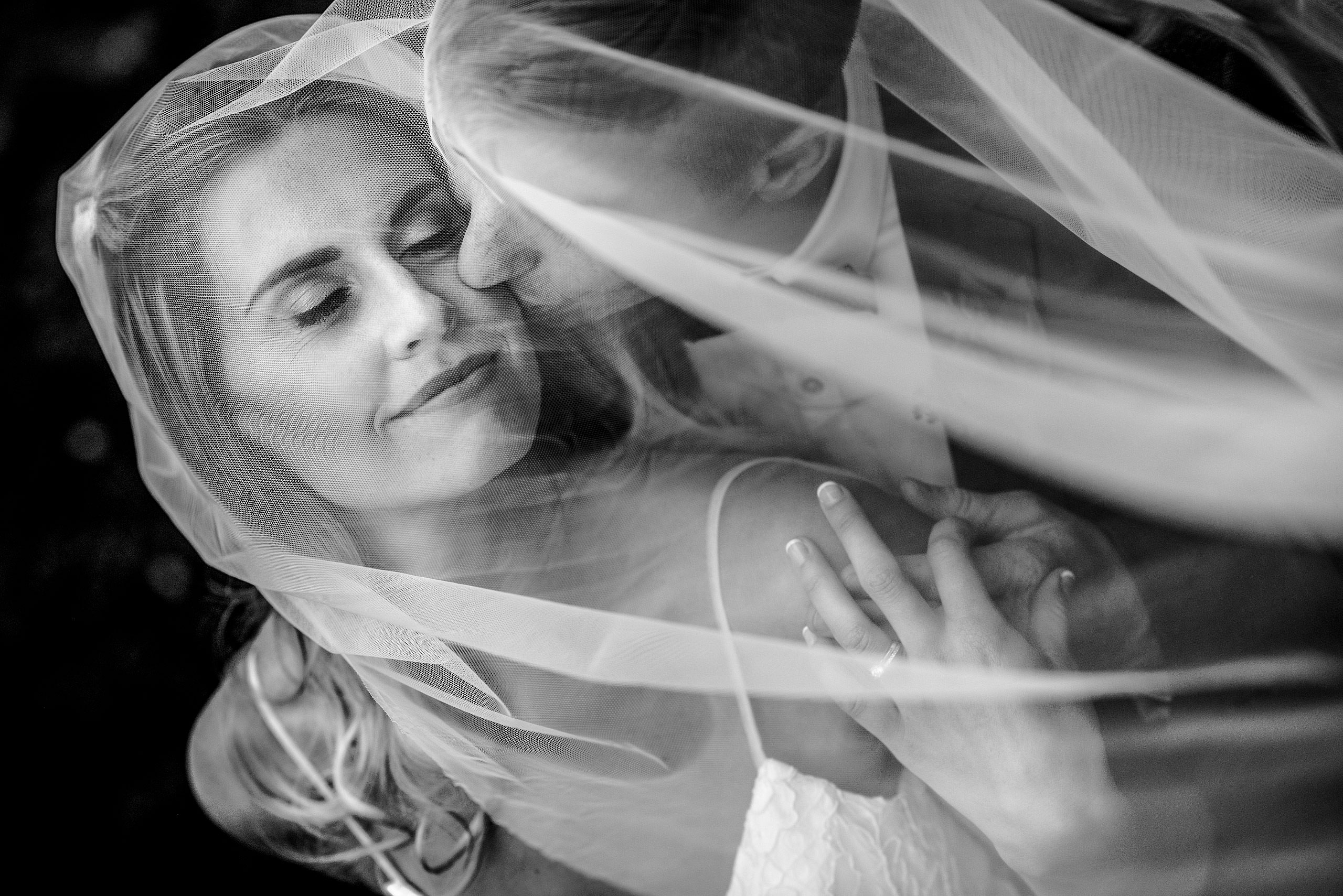 a groom kissing his bride under a veil be top calgary wedding photographer sean leblanc