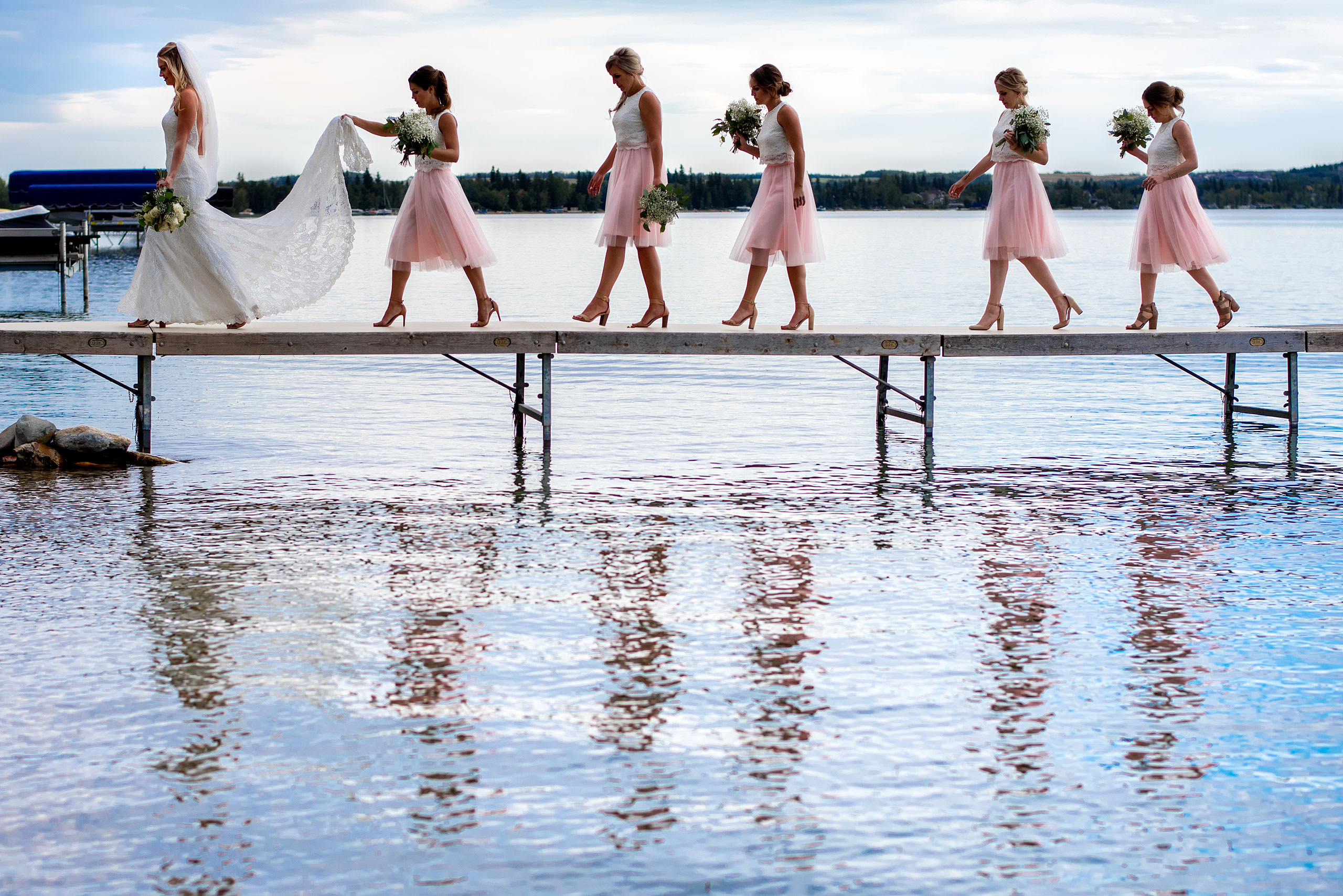 bridesmaids walking behind a bride on a dock by top calgary wedding photographer sean leblanc