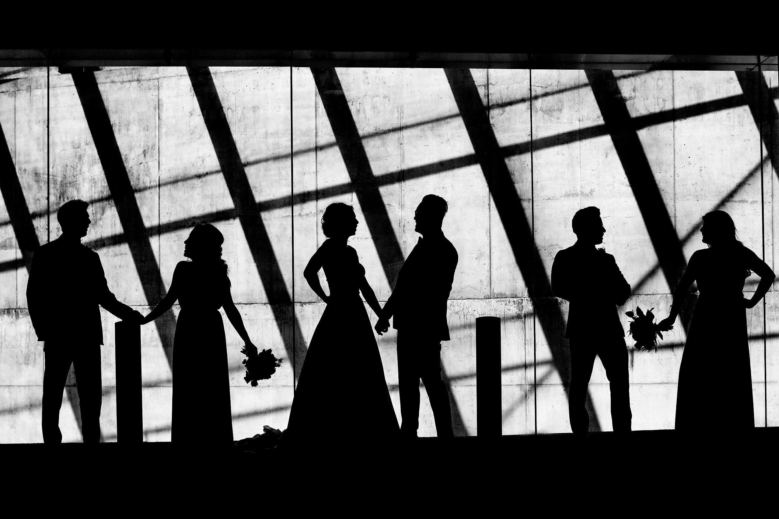 a bride party standing infant of a wall as a silhouette by top calgary wedding photographer sean leblanc
