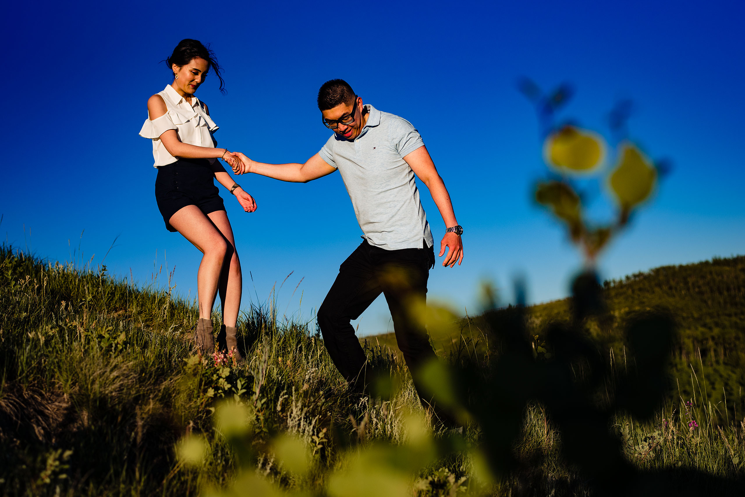 a man leading a women down a hill by top calgary engagement photographer sean leblanc